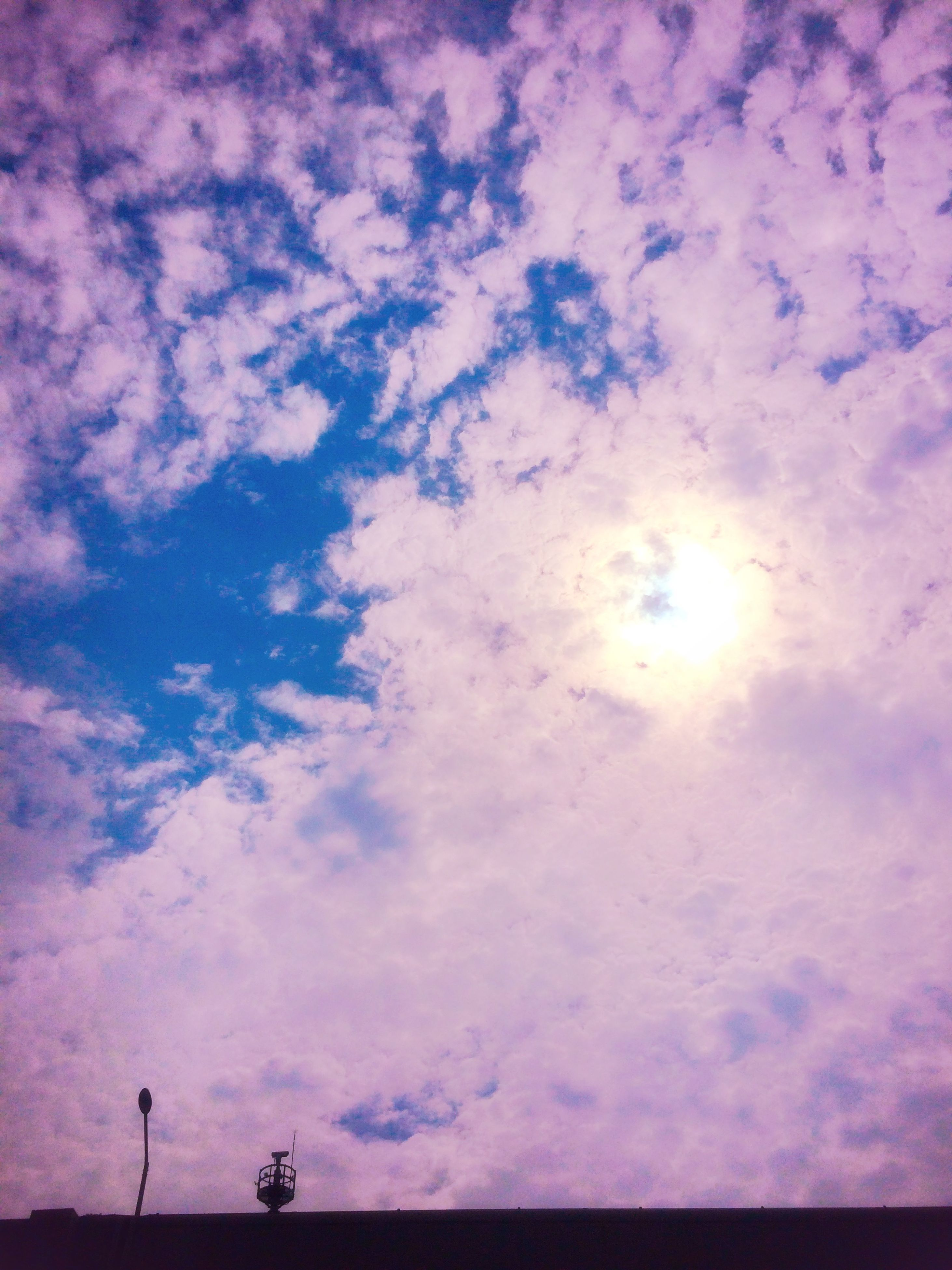 sky, silhouette, cloud - sky, low angle view, beauty in nature, tranquility, scenics, tranquil scene, nature, cloudy, sunset, cloud, sun, idyllic, sunlight, sunbeam, outdoors, cloudscape, weather, dusk