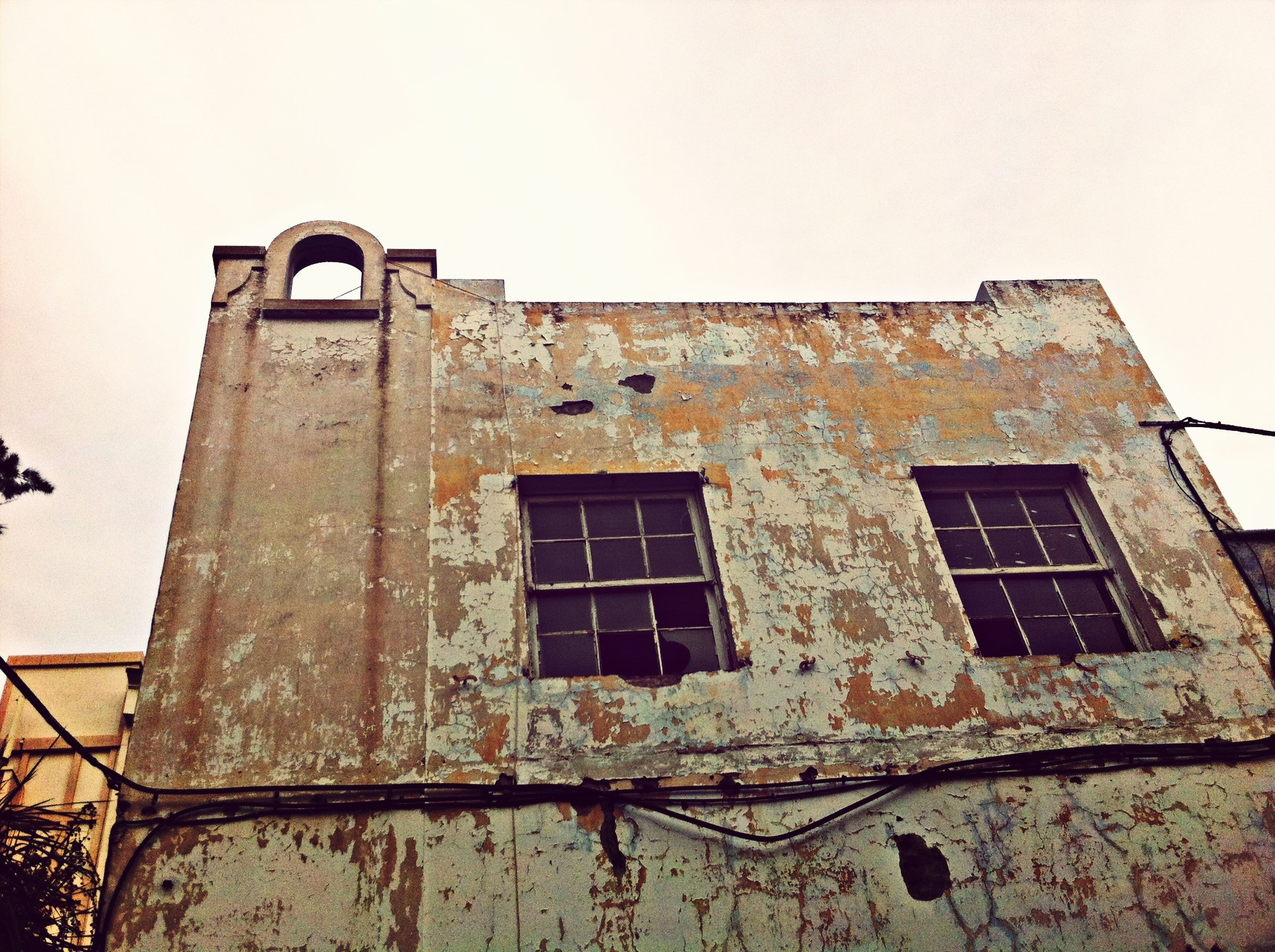 architecture, built structure, building exterior, window, low angle view, abandoned, old, damaged, obsolete, weathered, house, run-down, clear sky, deterioration, wall - building feature, bad condition, building, day, residential structure, outdoors