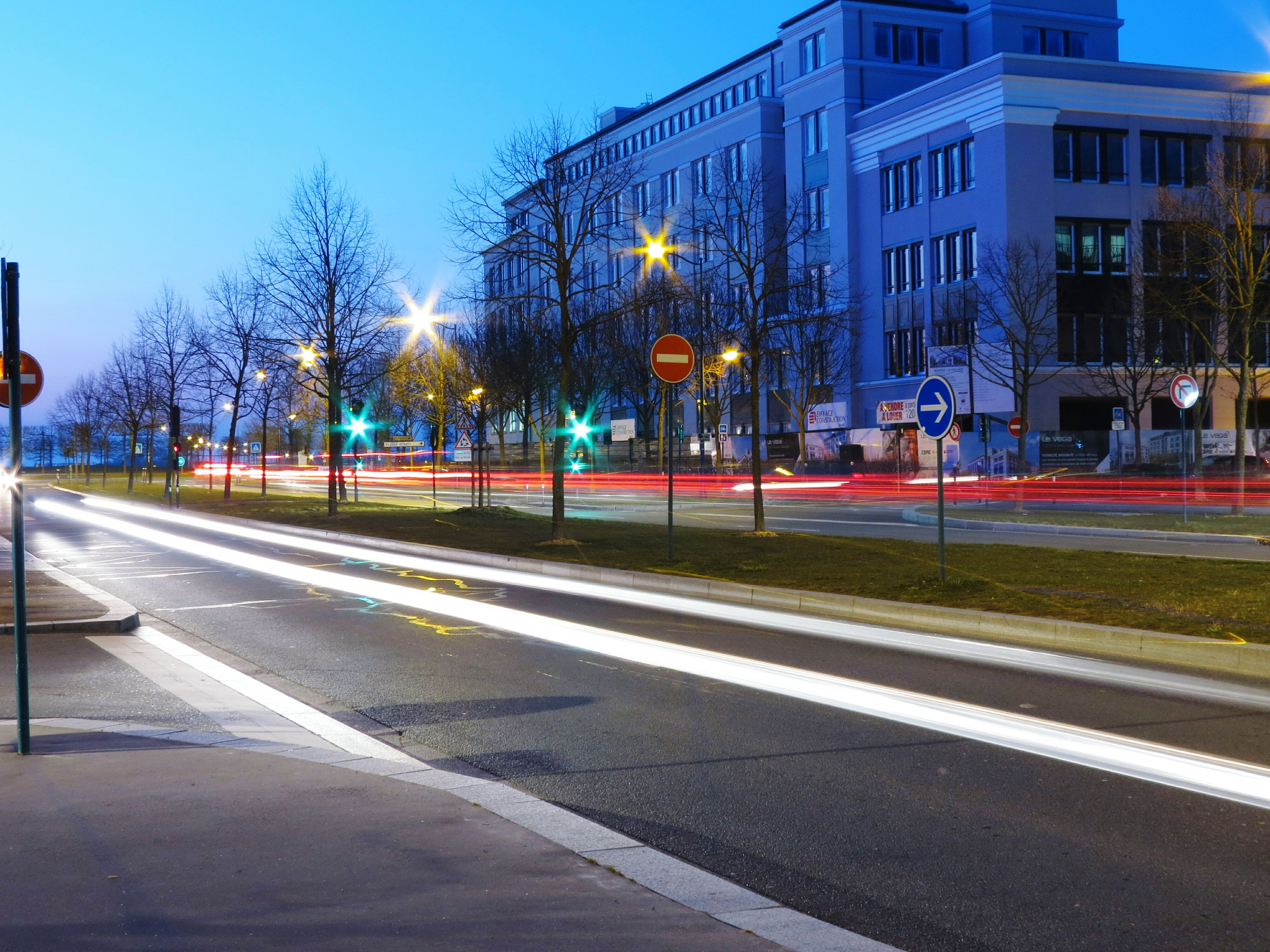 transportation, illuminated, road, building exterior, street light, street, city, road marking, long exposure, architecture, built structure, sky, light trail, night, speed, motion, the way forward, city street, car, clear sky