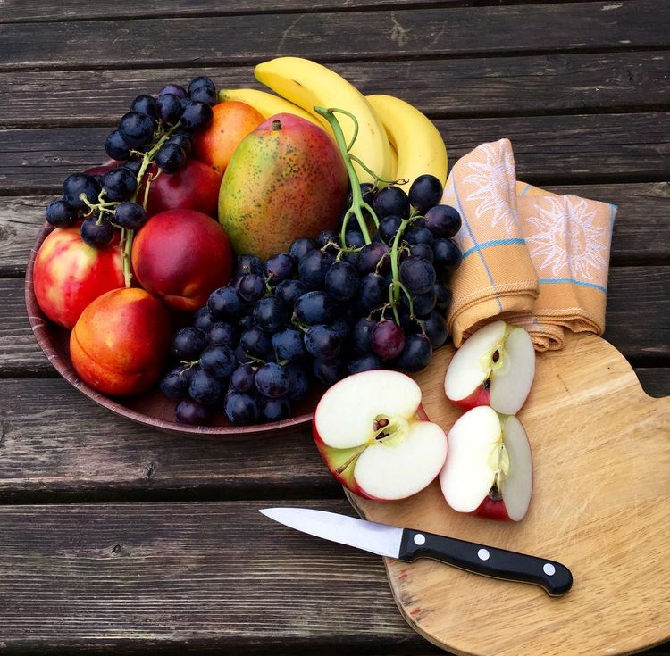 Fresh apples and fruits on a table Apple - Fruit Banana Basket Browm Close-up Cutting Board Food Freshness Grapes Grapes 🍇 Graphic Group Of Objects Halved Healthy Eating No People Organic Ripe SLICE Still Life Table Variation Wood Wood - Material Wooden