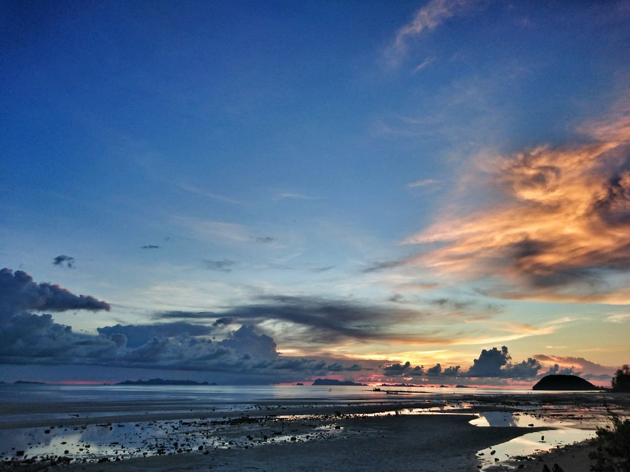 Scenic View Of Beach Against Cloudy Blue Sky At Dusk