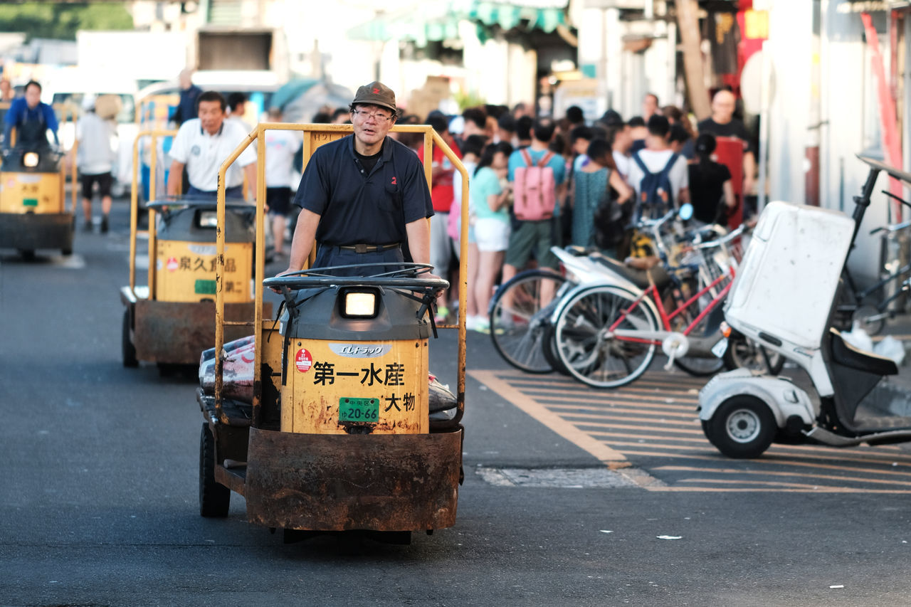 real people, incidental people, transportation, street, focus on foreground, mode of transport, men, one person, land vehicle, outdoors, day, road, full length, city, people