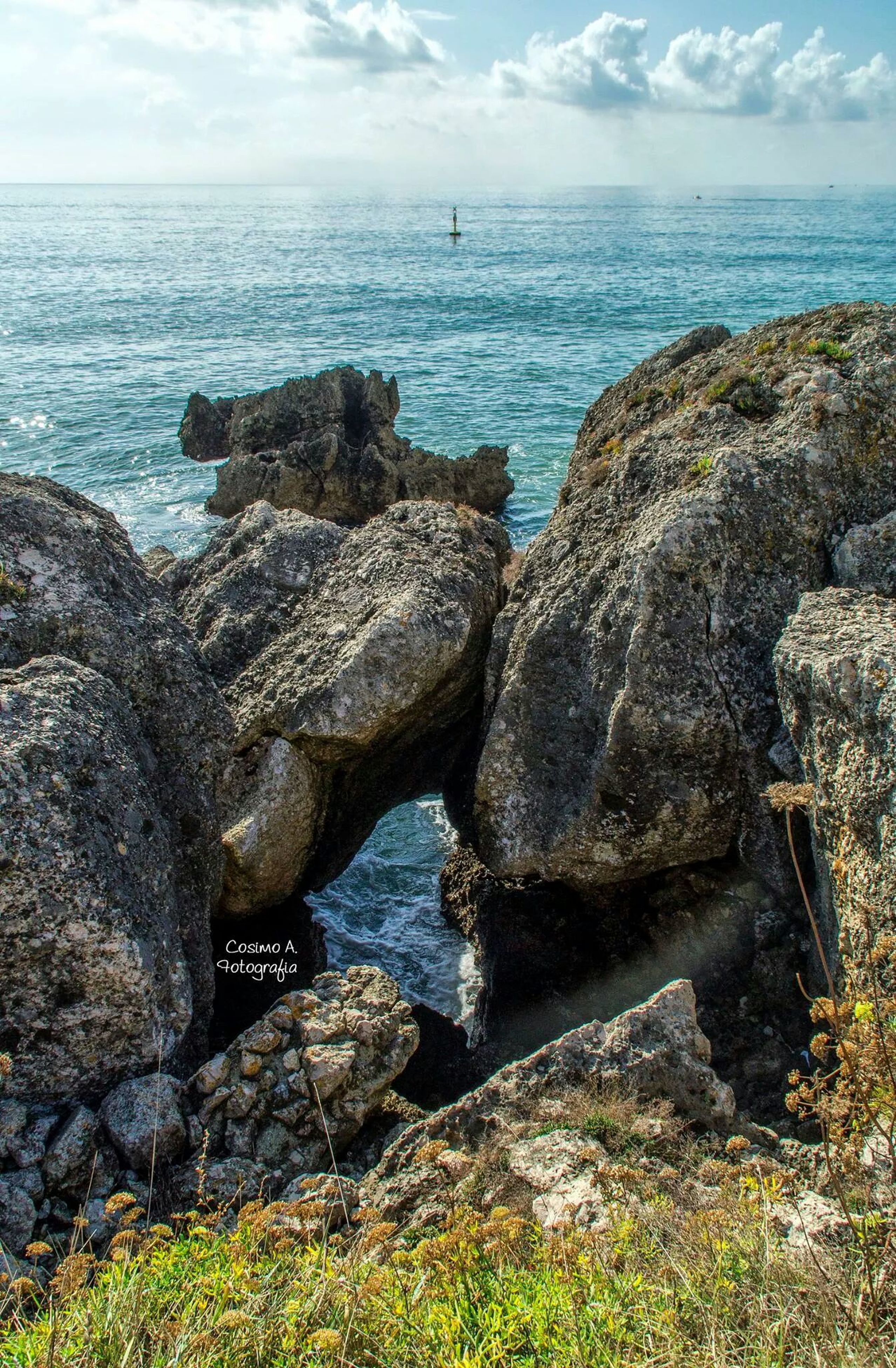 sea, water, horizon over water, tranquility, tranquil scene, scenics, sky, rock - object, beauty in nature, nature, rock formation, rock, shore, beach, idyllic, coastline, cliff, blue, high angle view, grass