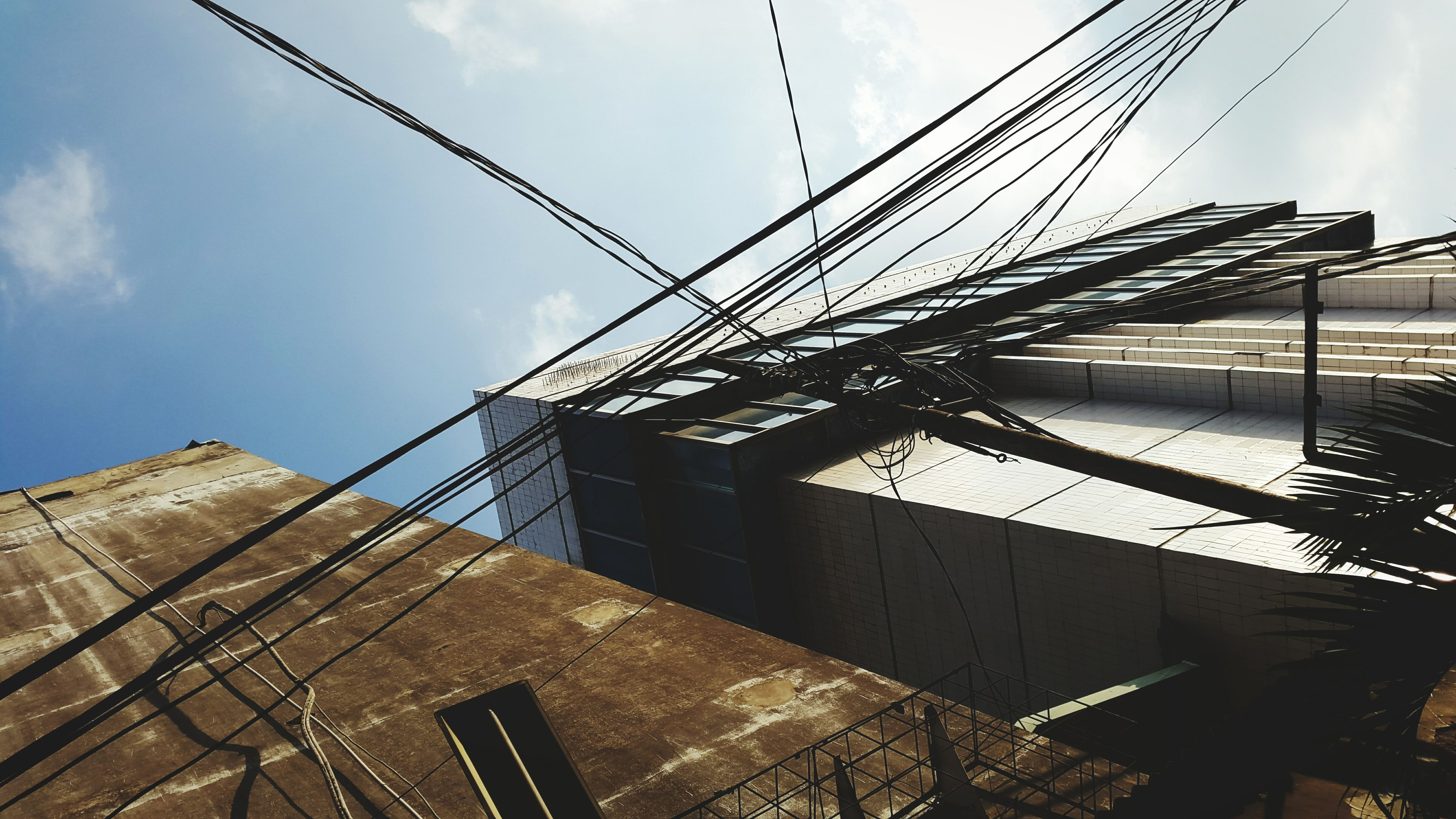 low angle view, sky, built structure, architecture, cloud - sky, building exterior, cloud, day, metal, cloudy, outdoors, connection, no people, tall - high, cable, electricity pylon, sunlight, power line, metallic, pattern