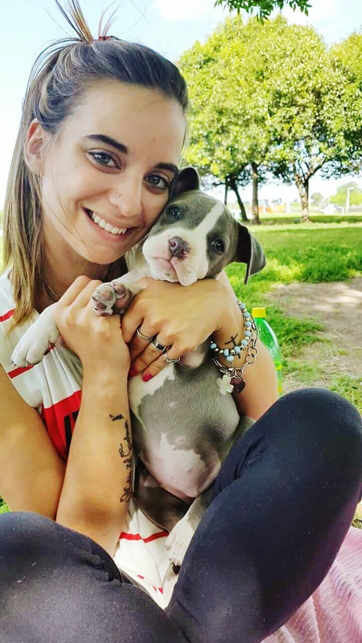 pets, dog, one animal, mammal, animal themes, domestic animals, real people, young women, looking at camera, one person, young adult, tree, casual clothing, holding, park - man made space, love, bonding, portrait, leisure activity, embracing, smiling, lifestyles, day, friendship, outdoors, one young woman only, people