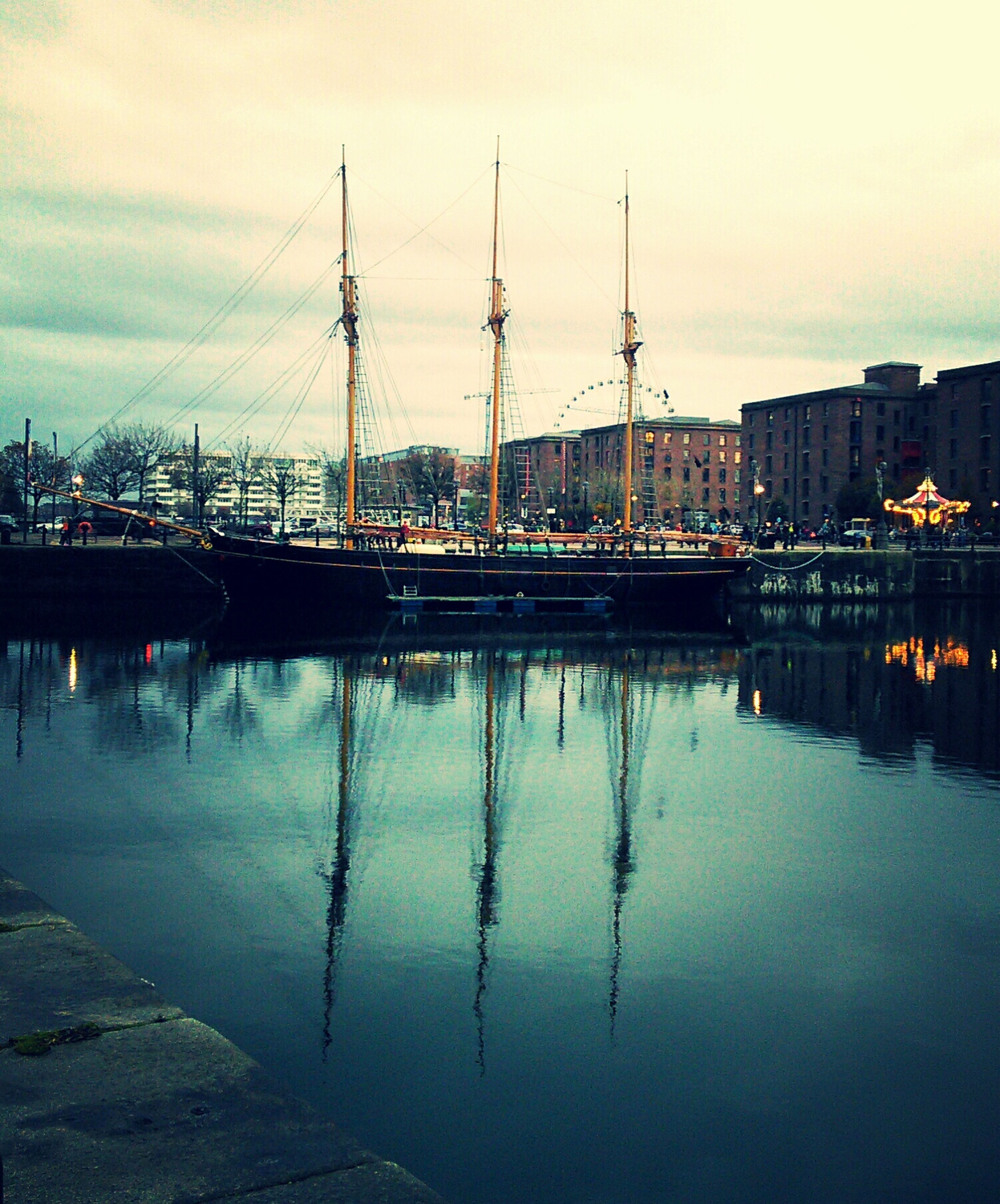 water, reflection, waterfront, nautical vessel, transportation, harbor, sky, moored, built structure, mast, mode of transport, river, boat, architecture, lake, sailboat, building exterior, nature, dusk, outdoors