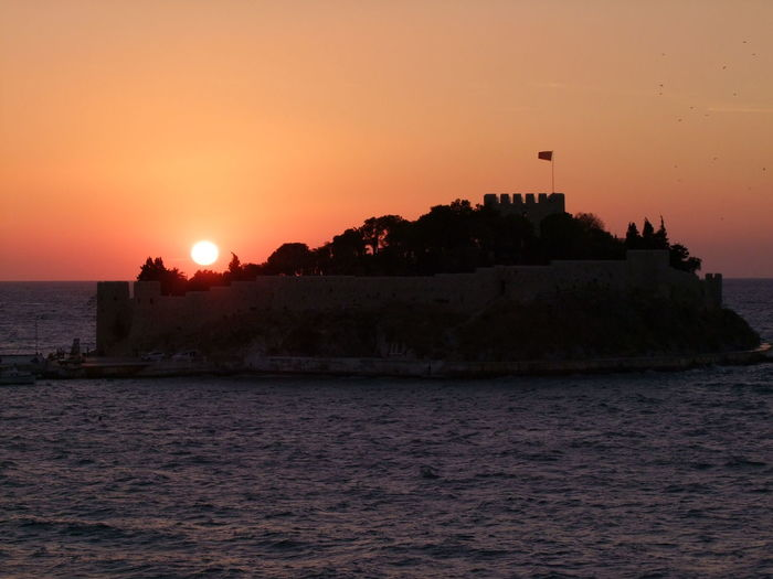 Sunset over Pidgeon Island, Kusadasi Beauty In Nature Castle Clear Sky Composition Fortress Full Frame Idyllic Island Kuşadası Orange Color Orange Sky Outdoor Photography Pidgeon Island Scenics Sea Silhouette Silhouette Sun Sunlight Sunset Tourist Attraction  Tranquil Scene Tranquility Turkey Water