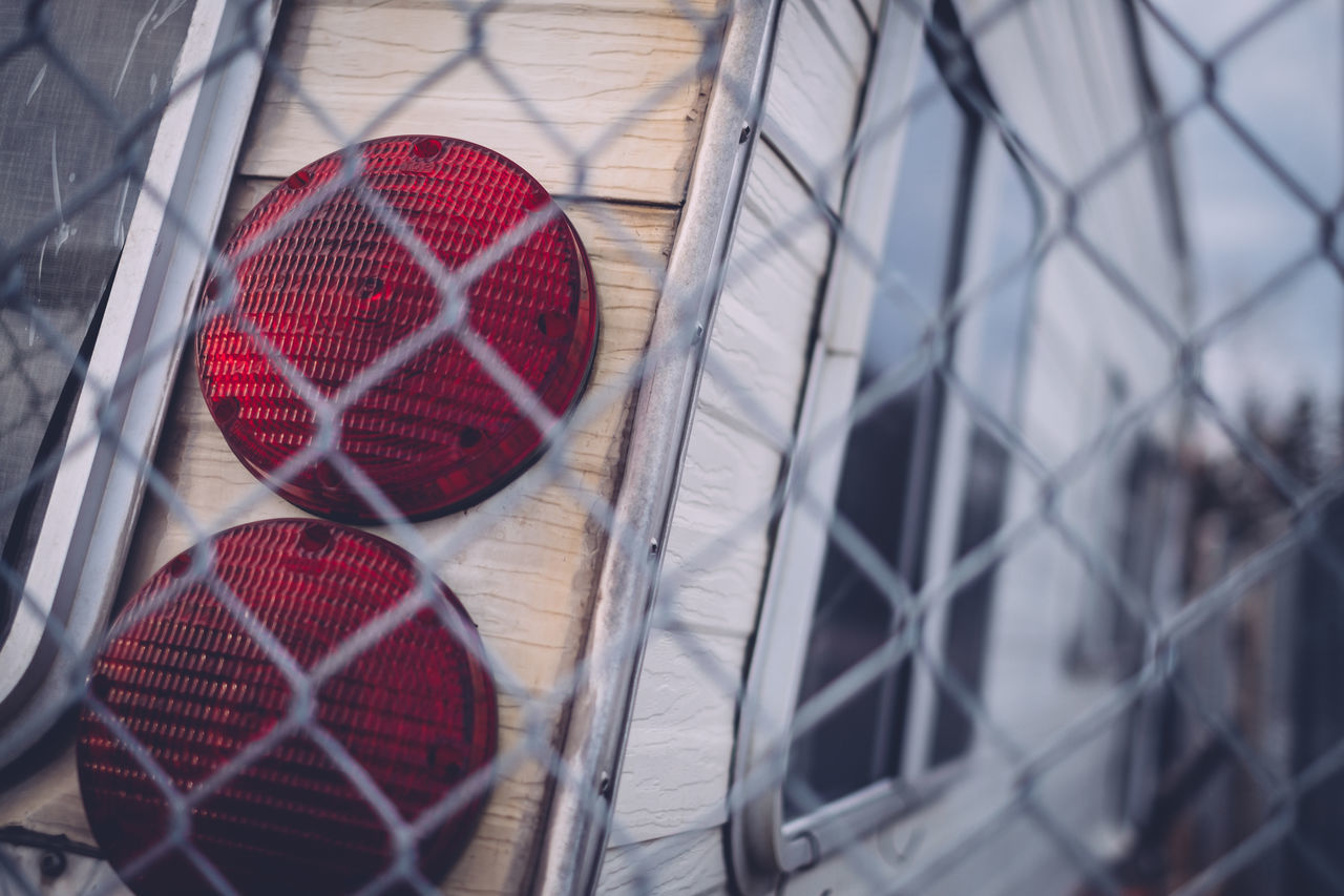 Chainlink Fence Close-up Day No People Outdoors Protection Red Red Lights Selective Focus Shooting Through Tail Lights Trailer