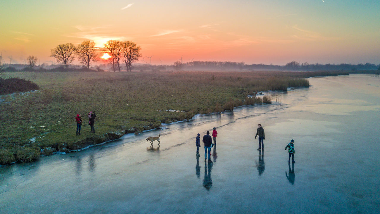 """Sunset in Zaamslag Two young families and their dog test out the fresh ice on the south part of the Otheensche Kreek during sunset in Zaamslag, Zeeuws Vlaanderen (DJI FC220 26.3 mm f/2.2 ƒ/2.2 4.7mm 1/370"""" iso 100) Adult Children Day Dog Dronephotography Family Horizon Ice Landscape Natural Ice Nature Netherlands Outdoors People Reflection Scenics Season  Sky Sun Sunday Sunset View From Above Water Winter Zeeland"""