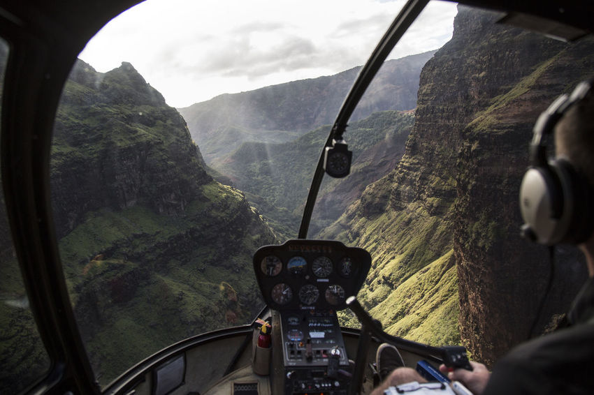View from Helicopter at waimea valley Gorge Hawaii Waimea Canyon Air Vehicle Close-up Cockpit Day Flying Helicopter Helicopter View  Indoors  Landscape Mode Of Transport Mountain Mountain Range Mountains And Valleys Nature One Person Pilot Real People Rugged Landscape Sky Tree Vehicle Interior Windshield