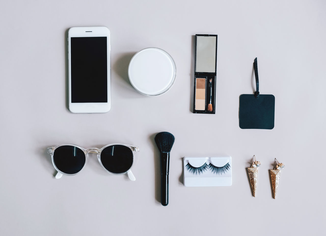 Earrings Fashion Makeup Objects Woman Arrangement Beauty Brush Cosmetics Day Eyelash Flatlay Indoors  Mobile Phone No People Portable Information Device Powder Smart Phone Still Life Studio Shot Sunglasses Technology Top View White Background Wireless Technology