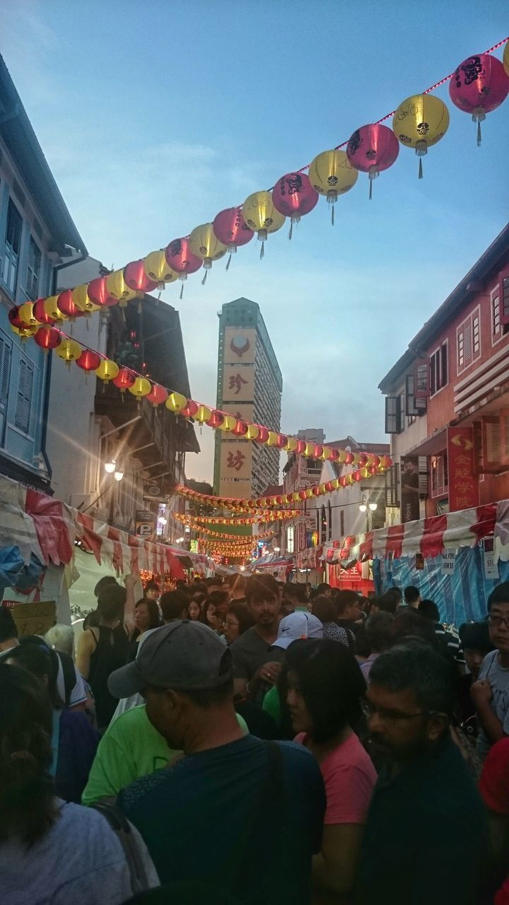 large group of people, hanging, celebration, building exterior, lighting equipment, architecture, illuminated, built structure, street, chinese lantern, paper lantern, sky, city, lantern, traditional festival, men, market, night, real people, crowd, low angle view, women, outdoors, multi colored, people