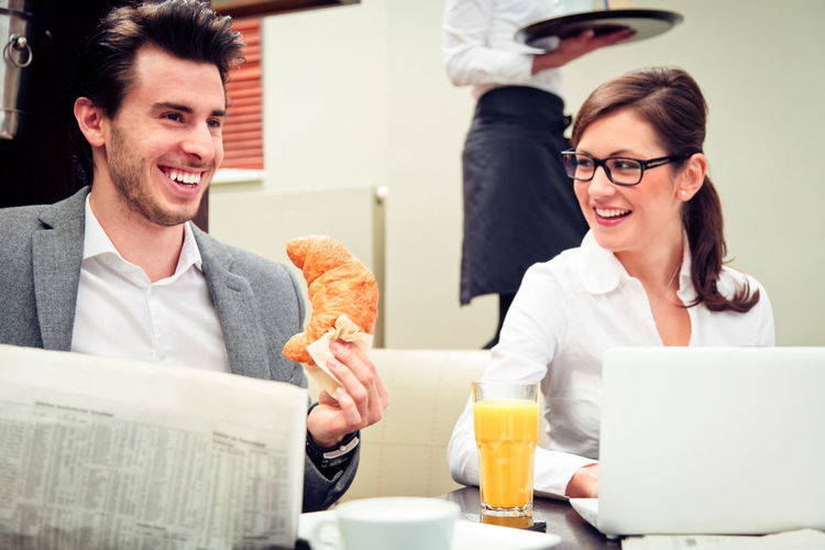Business people at a cafe Breakfast Business Business People Businessman Cafe Coffee Break Drinking Eyeglasses  Fashion Indoors  Laptop Men Restaurant Sitting Stylish Success Team Teamwork Technology Two People Using Laptop Waiter Wireless Technology Working Young Women