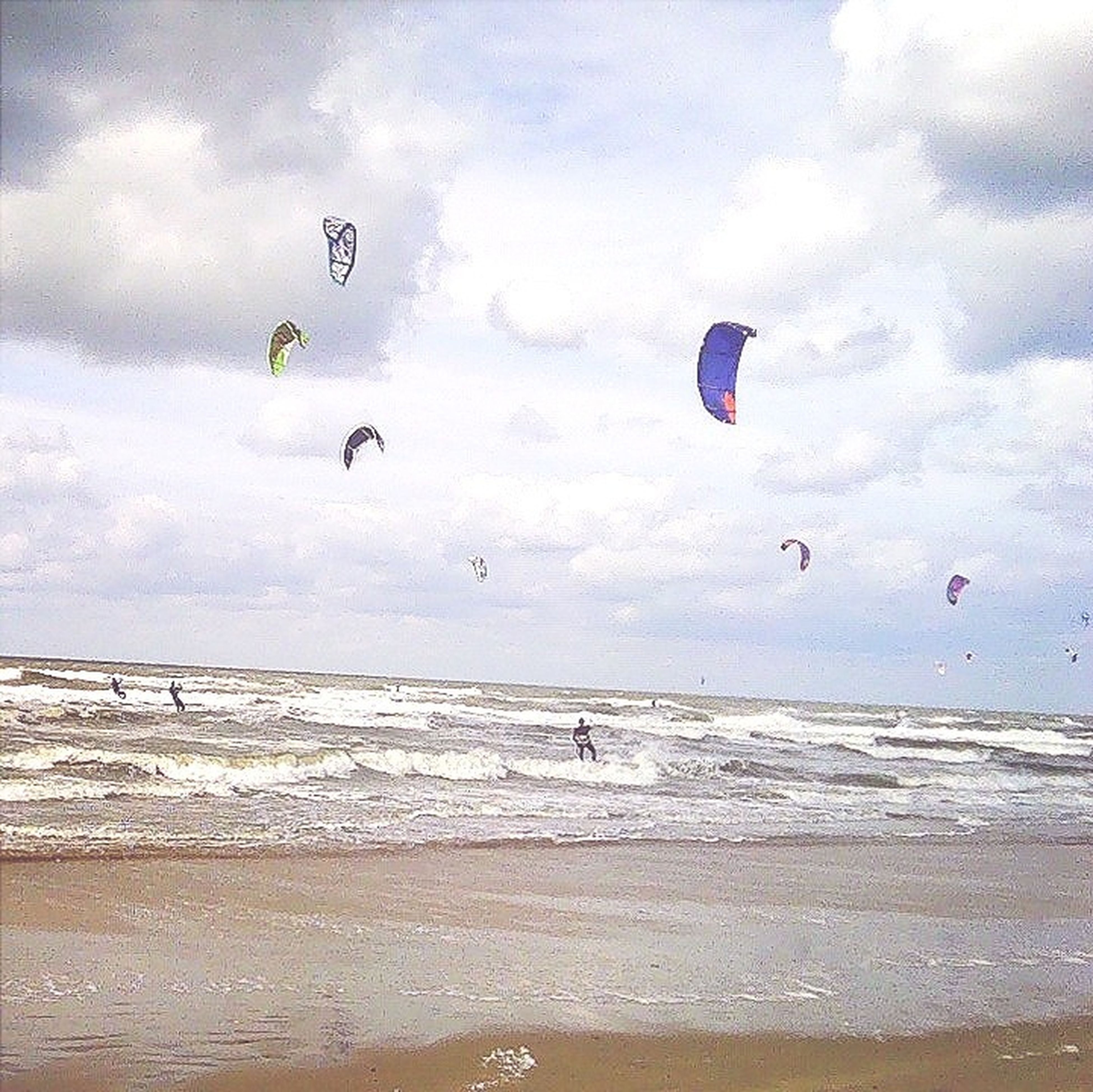 beach, flying, parachute, sea, sky, mid-air, adventure, paragliding, extreme sports, water, sport, scenics, tranquility, sand, cloud - sky, beauty in nature, leisure activity, shore, vacations, nature