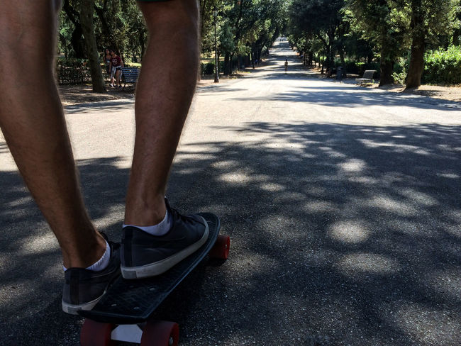 Casual Clothing Cropped Day Footpath Footwear Having Fun Leisure Activity Lifestyles Low Section Outdoors Park Part Of Pennyboard Person Personal Perspective Road Skateboarding Sports Summer Sunlight The Way Forward Tree Tree Trunk Unrecognizable Person Villa Borghese Park