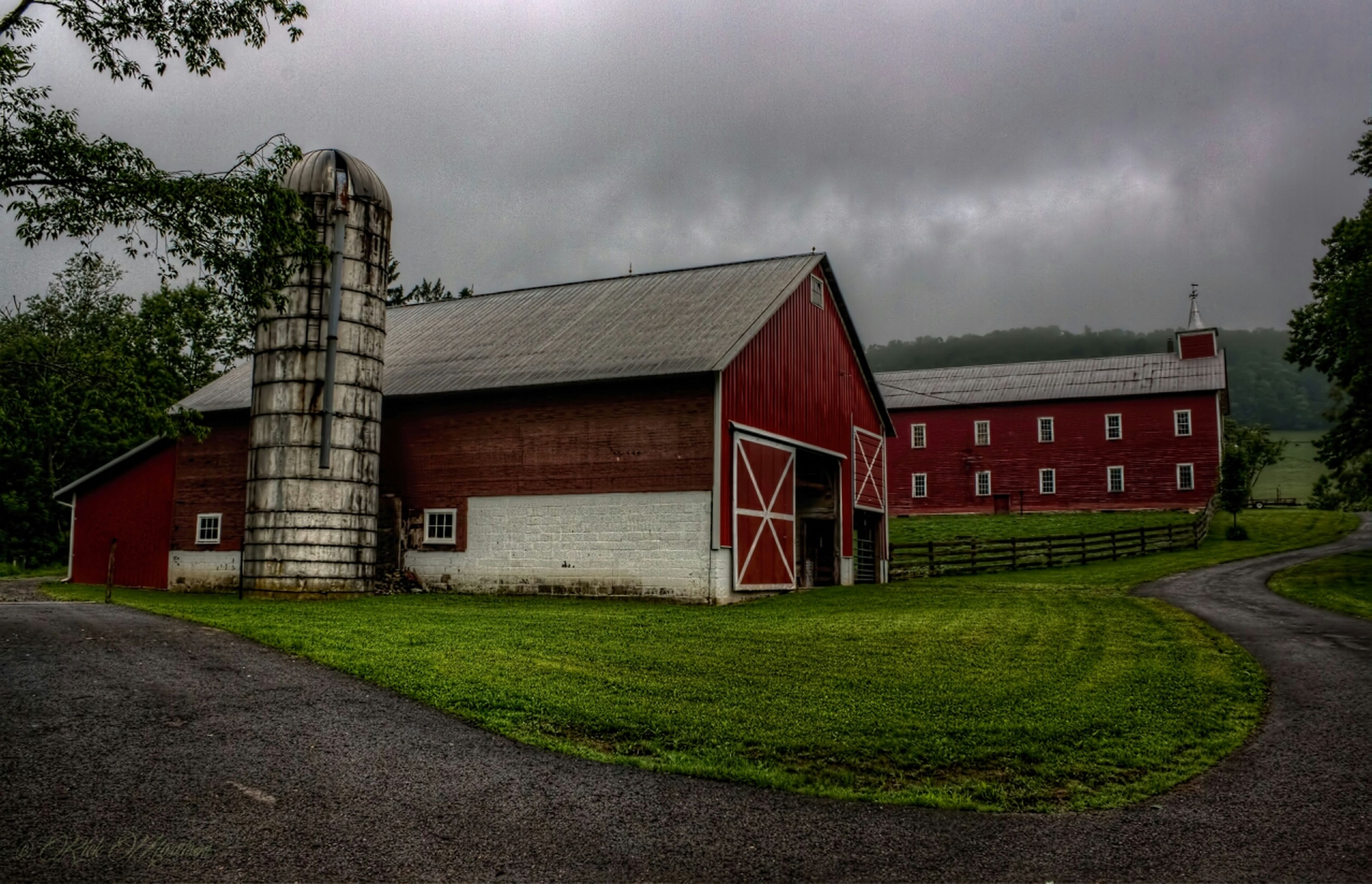 architecture, building exterior, built structure, sky, grass, cloud - sky, house, cloudy, field, grassy, overcast, cloud, residential structure, green color, outdoors, rural scene, barn, no people, day, tree
