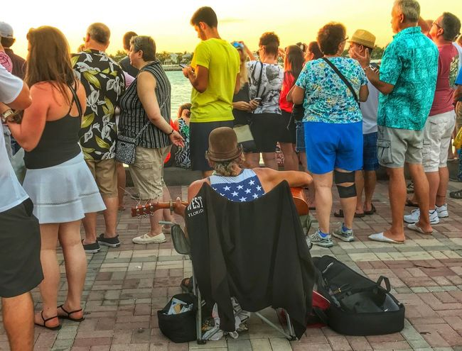 Street Performer All Eyes On The Sunset not really ignoring him Playing For The People Sunset Celebration Mallory Square Sunset Large Group Of People Lifestyles Togetherness The Week On EyeEm Breathing Space