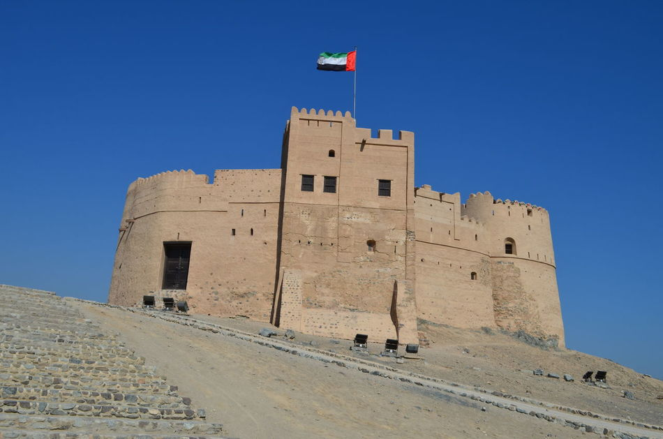 Architecture Blue Sky Built Structure Day Flag Fort Fortress Fujairah Historical Building History Man Made Structure No People Outdoors Travel Travel Destinations UAE United Arab Emirates