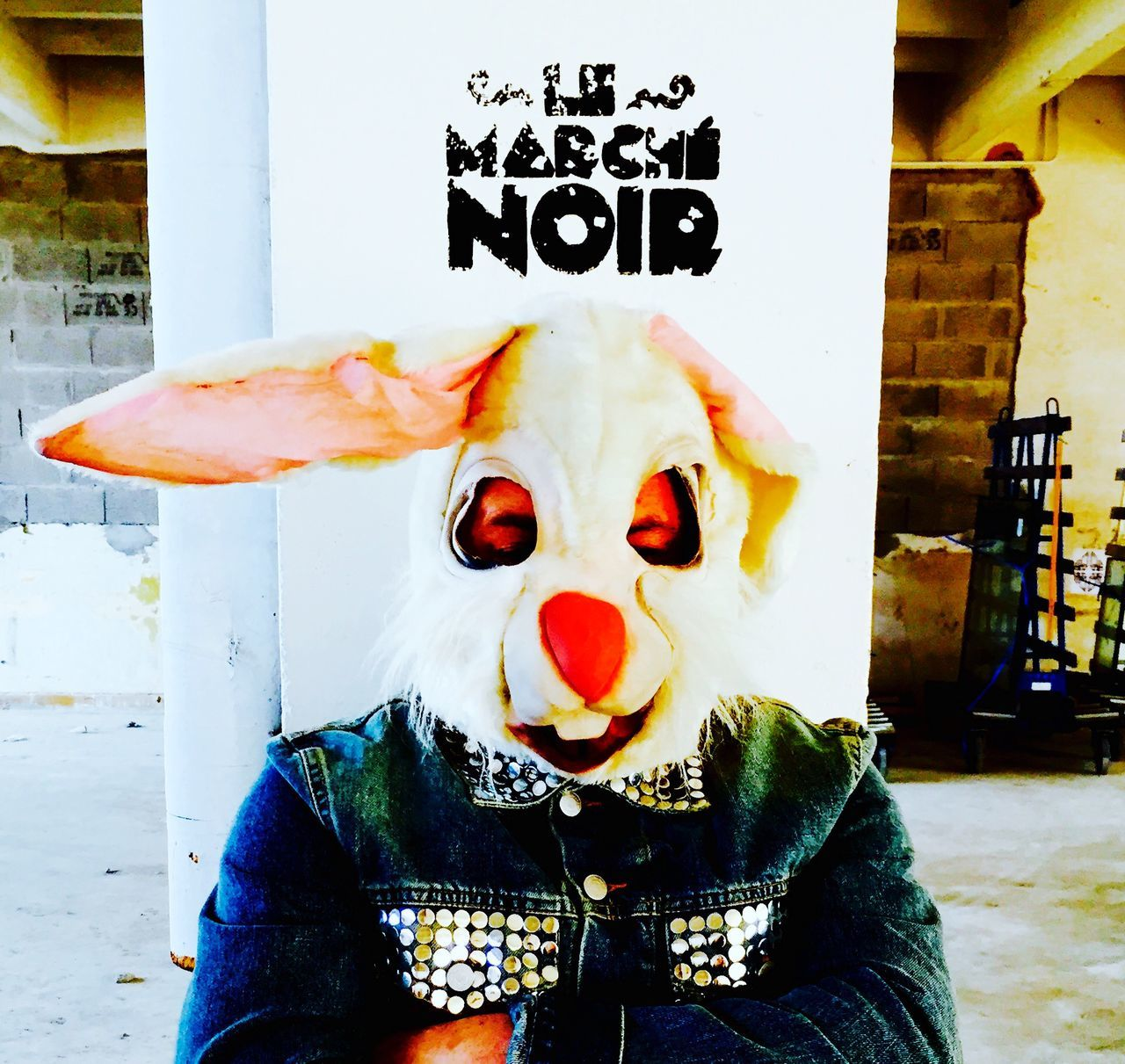 Man In Rabbit Mask Against Column In Building
