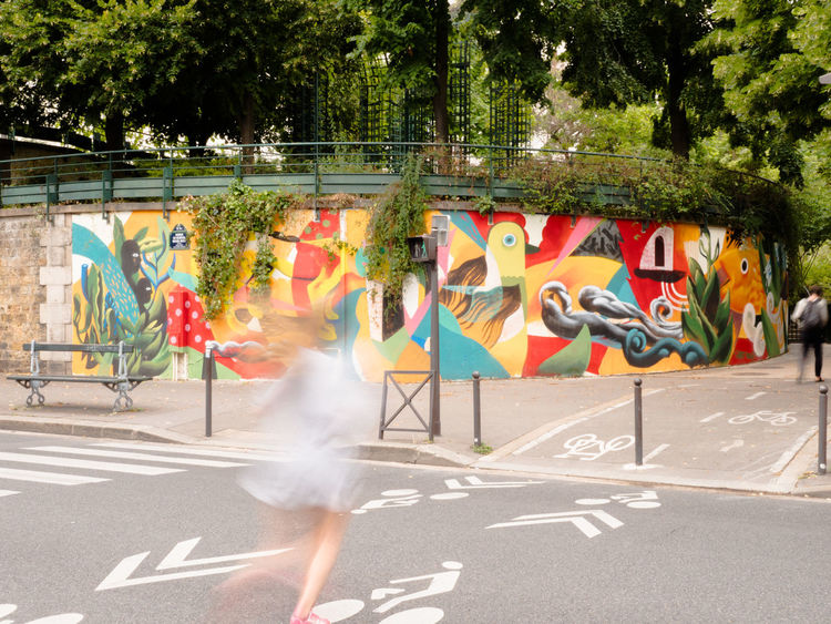 Crossing The Street Paris Running Silhouette Street Art/Graffiti Wall Woman Adult City Day Full Length Lifestyles Long Exposure Motion Multi Colored One Person Outdoors Painting People Road Skill  Street Art Street Photography Streetphotography Tree