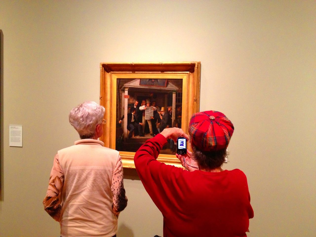 real people, rear view, photographing, photography themes, technology, men, two people, indoors, lifestyles, wireless technology, leisure activity, standing, camera - photographic equipment, cellphone, women, communication, togetherness, architecture, photo messaging, day