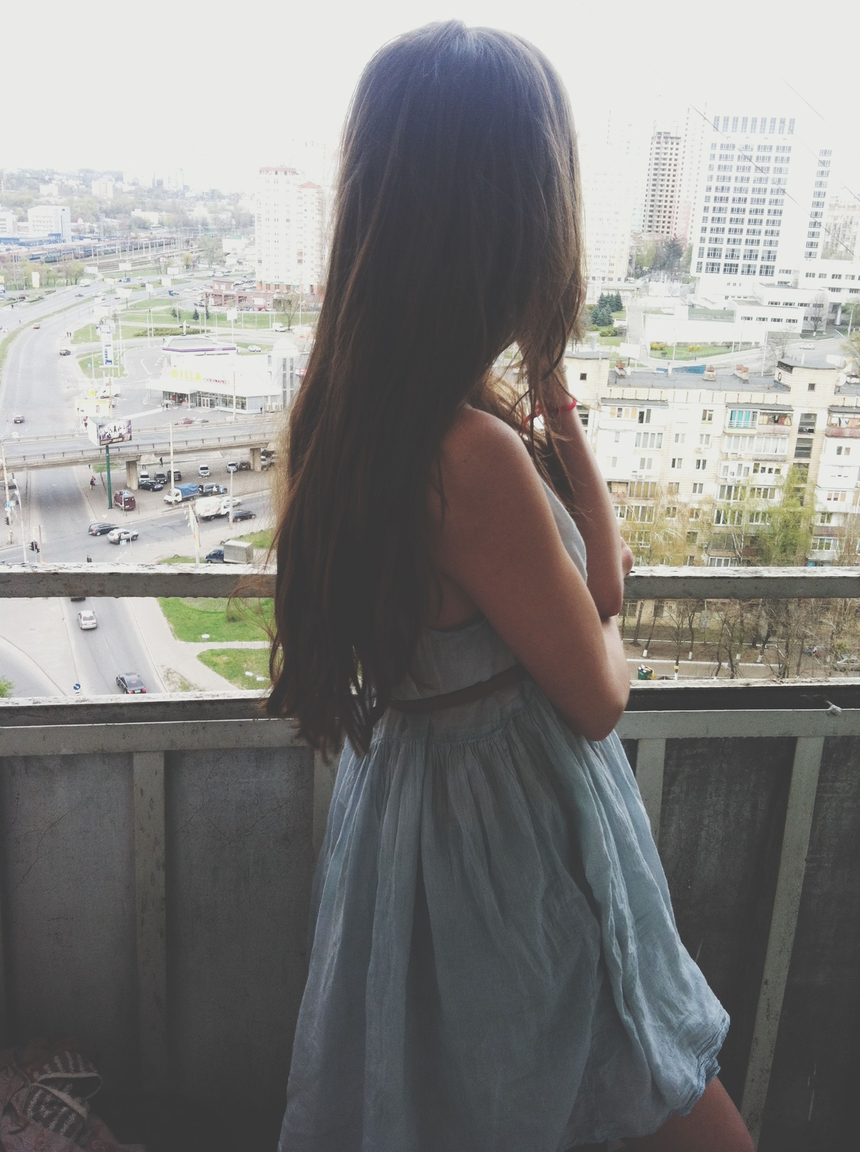 rear view, lifestyles, waist up, architecture, building exterior, city, built structure, leisure activity, long hair, casual clothing, cityscape, person, sitting, young women, three quarter length, young adult, standing, focus on foreground