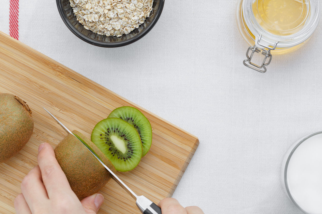 Close-up Cutting Board Day Food Food And Drink Freshness Fruit Healthy Eating High Angle View Human Body Part Human Hand Indoors  Kiwi One Person People SLICE Table