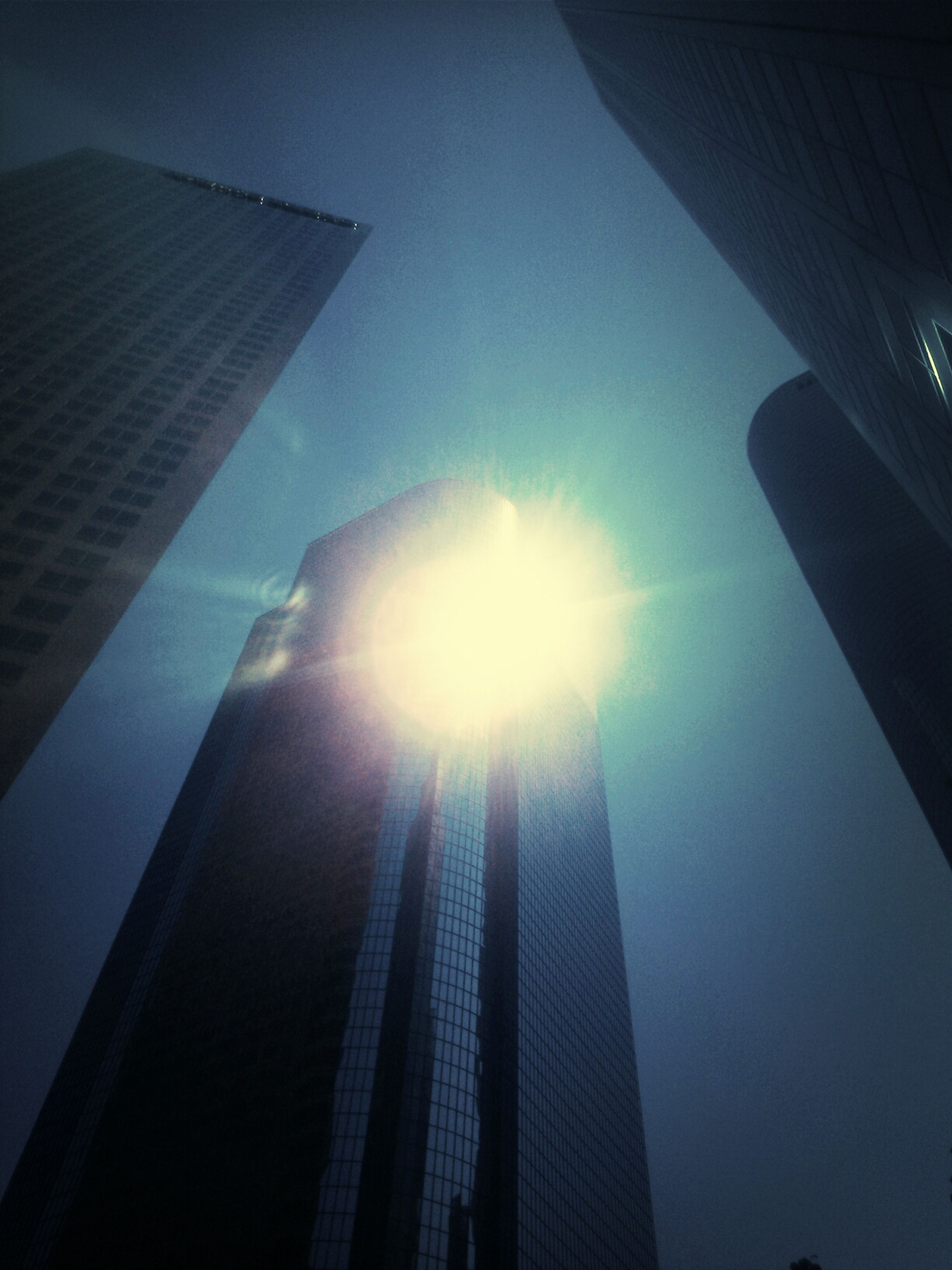 low angle view, architecture, sun, built structure, sunbeam, building exterior, lens flare, sunlight, sky, tall - high, skyscraper, tower, modern, bright, office building, city, silhouette, directly below, glass - material, building