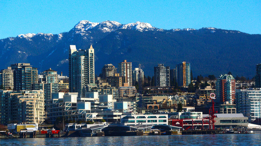 North Vancouver B.C. with snow capped mountains. Lonsdale Quay North Vancouver B.C. Canada Skyscraper Cityscape Architecture Building Exterior Urban Skyline City Built Structure No People Mountain Sky