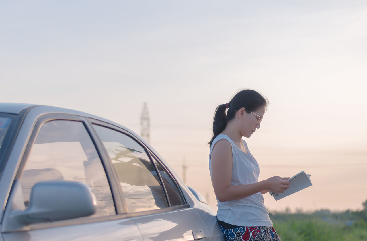 Adult Adults Only Car Casual Clothing Communication Day Holding Land Vehicle Lifestyles Mode Of Transport Nature One Person One Young Woman Only Outdoors People Real People Side View Sky Standing Technology Reading A Book Women Young Adult Young Women