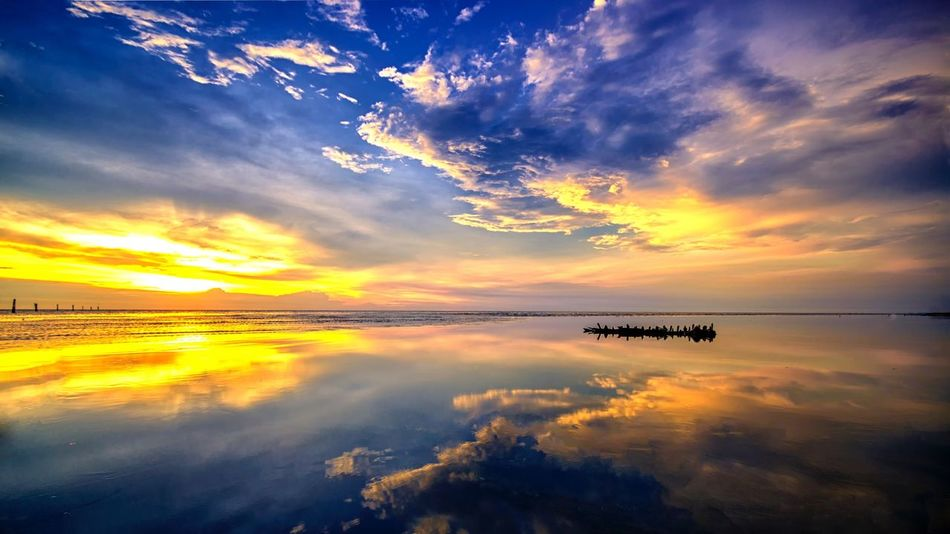 Sunset reflection during evening Nature Photography Moments Landscape_Collection The Great Outdoors With Adobe Wide Angle Clouds And Sky My Favorite Photo Golden Hour Sunset Sillouette Slowshutter Beach Ocean View Sea Reflection Wrecked Boat.
