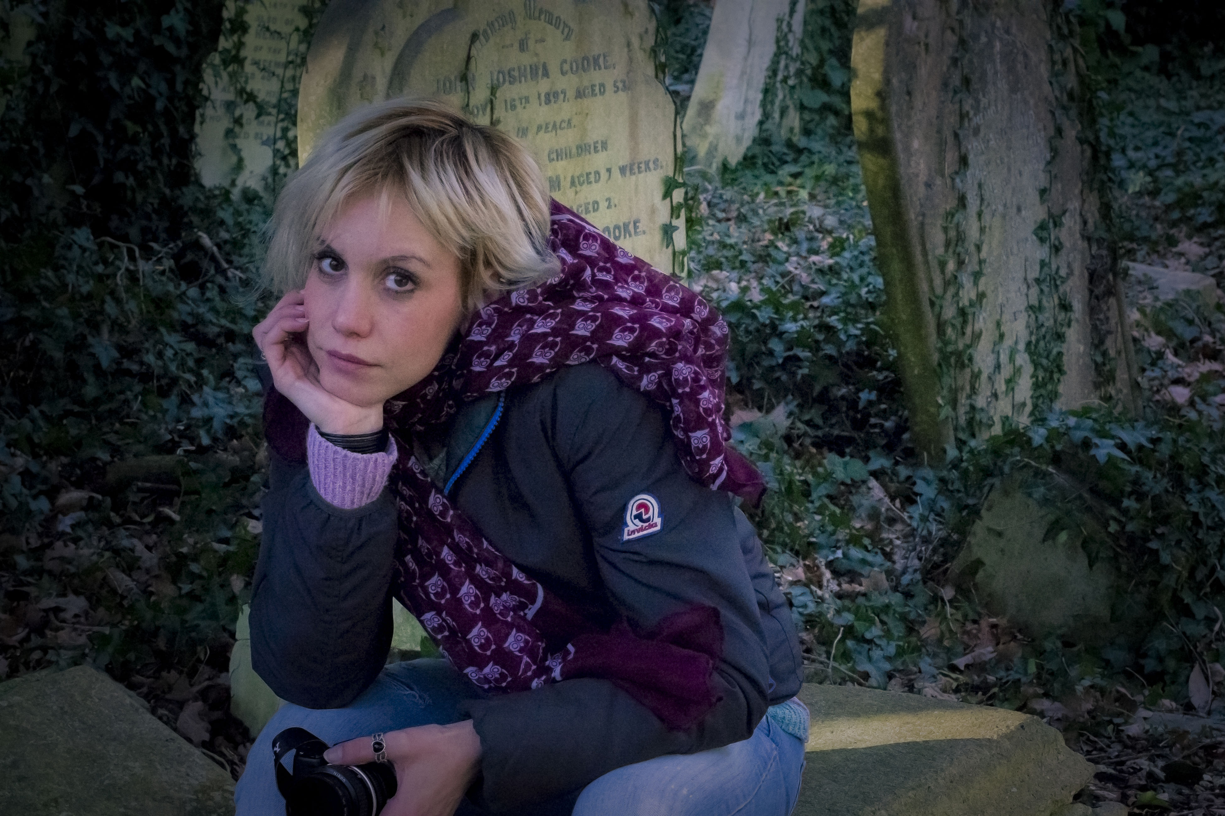 one person, real people, sitting, lifestyles, blond hair, young women, looking at camera, young adult, front view, casual clothing, outdoors, day, beautiful woman, portrait, architecture, tree, people