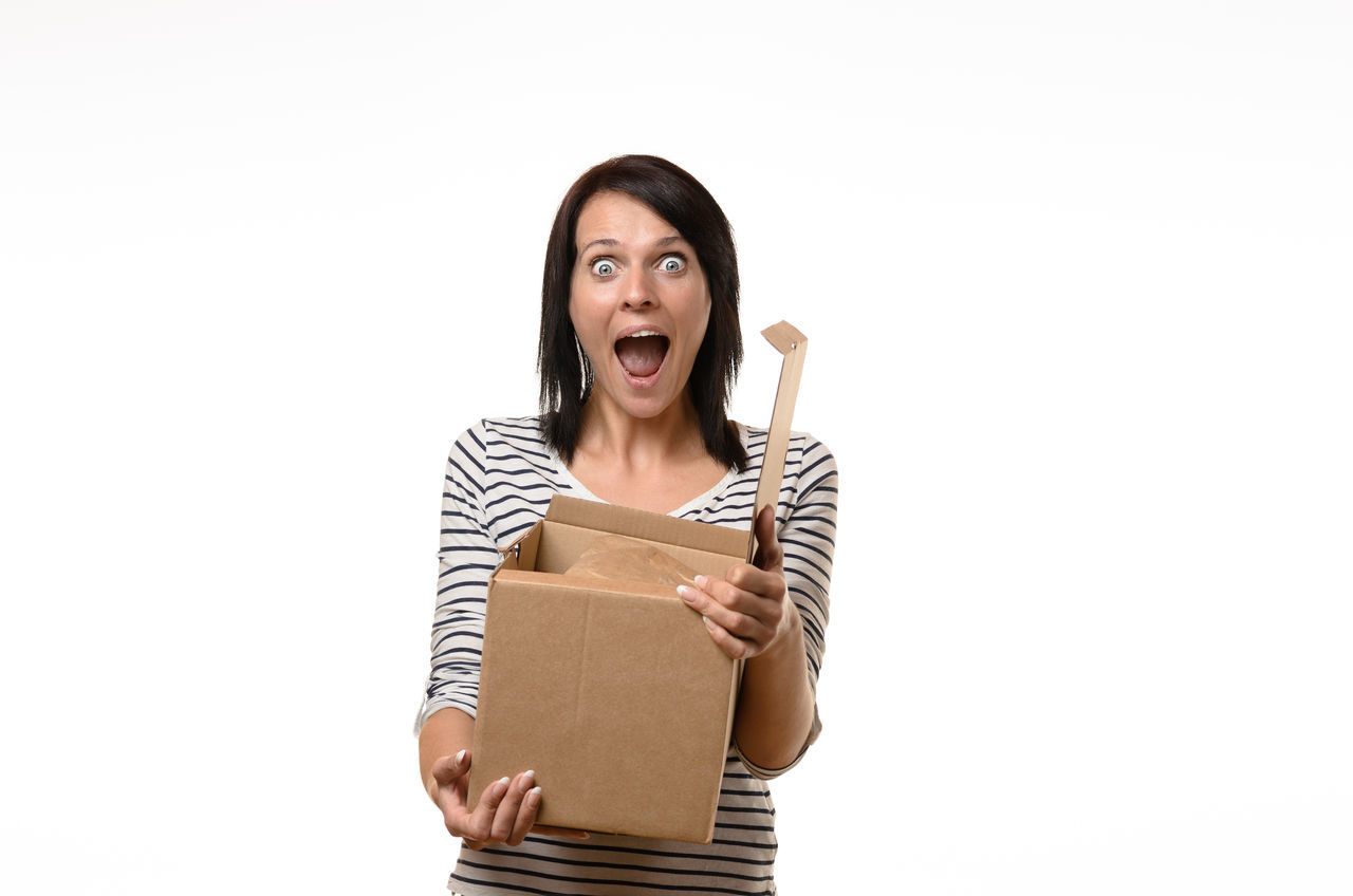 Adult Adults Only Box - Container Cardboard Box Disbelief Excitement Gasping Human Body Part Human Mouth Indoors  Mouth Open Occupation One Person One Woman Only One Young Woman Only Only Women Open People Shock Studio Shot Surprise White Background Women Young Adult Young Women