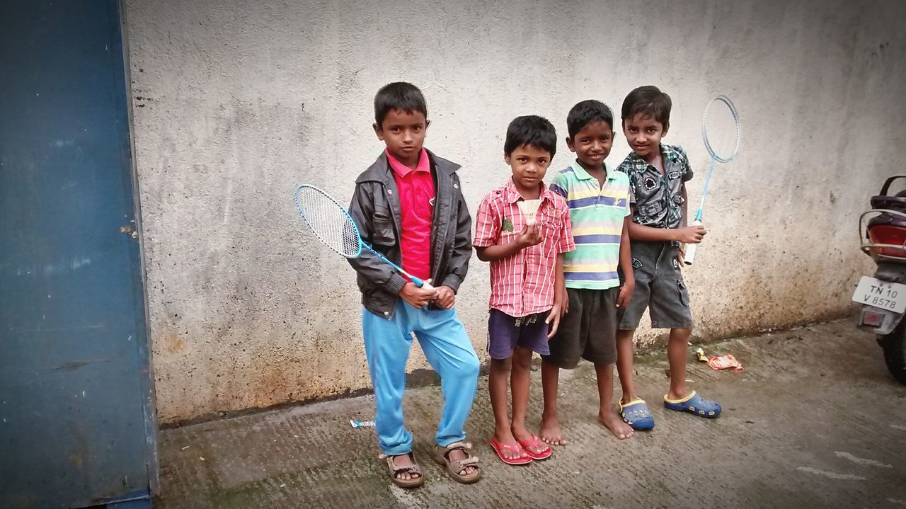 full length, standing, looking at camera, boys, portrait, togetherness, casual clothing, girls, childhood, front view, happiness, elementary age, day, child, smiling, outdoors, real people, friendship, bonding, architecture, people, young adult, adult