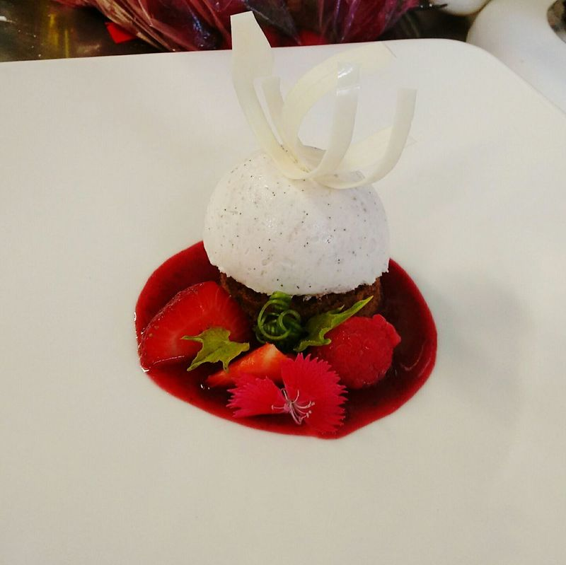 My World Of Food vanilla bean mousse over a coffee biscuit, strawberry and raspberry coulis, white chocolate curl.