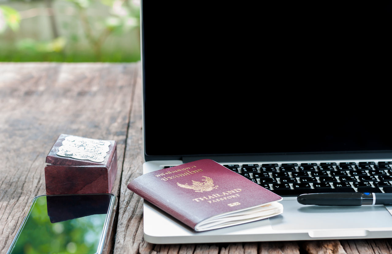 Laptop with smart phone and passport on the table Box Close-up Communication Day Indoors  Keyboard Laptop No People Open Passport Pen Smart Phone Table Technology Wireless Technology