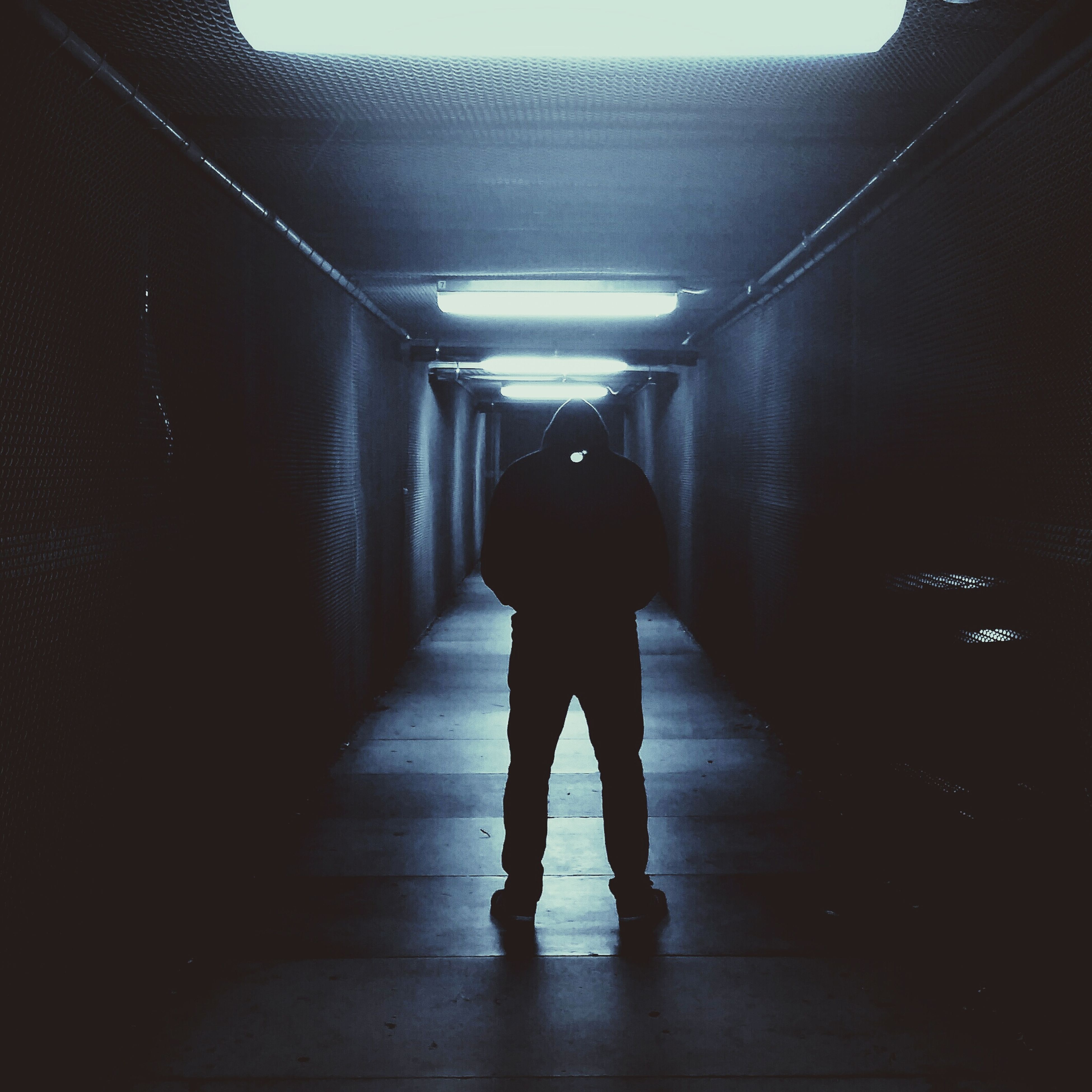 indoors, full length, rear view, tunnel, walking, the way forward, lifestyles, illuminated, corridor, men, architecture, built structure, wall - building feature, standing, silhouette, ceiling, lighting equipment, diminishing perspective