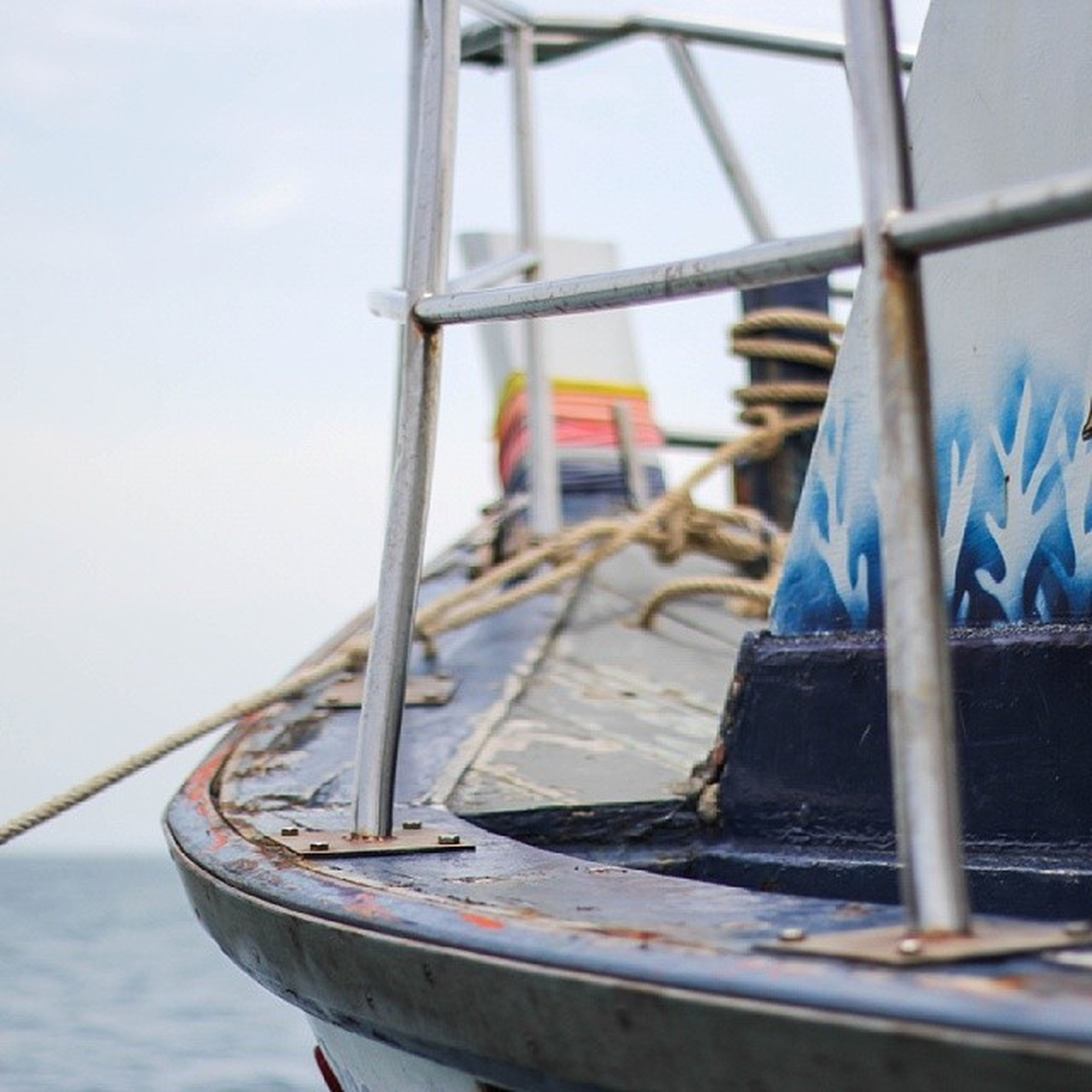 nautical vessel, boat, moored, water, mode of transport, transportation, sea, focus on foreground, rope, sky, day, metal, close-up, outdoors, blue, no people, abandoned, damaged, old, wood - material