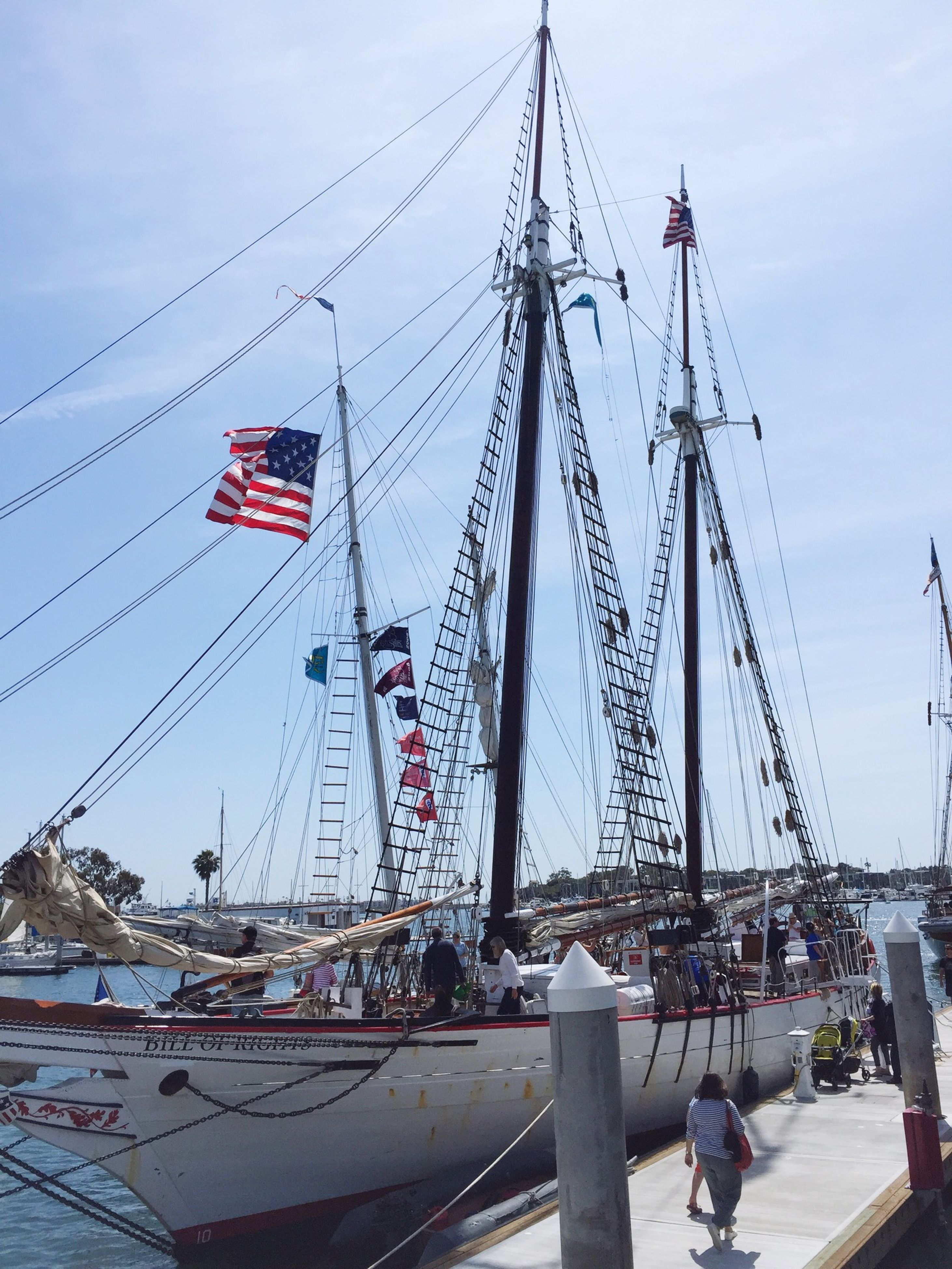 transportation, nautical vessel, mode of transport, mast, sky, flag, travel, large group of people, harbor, men, boat, sailboat, day, built structure, leisure activity, outdoors, travel destinations, low angle view, incidental people