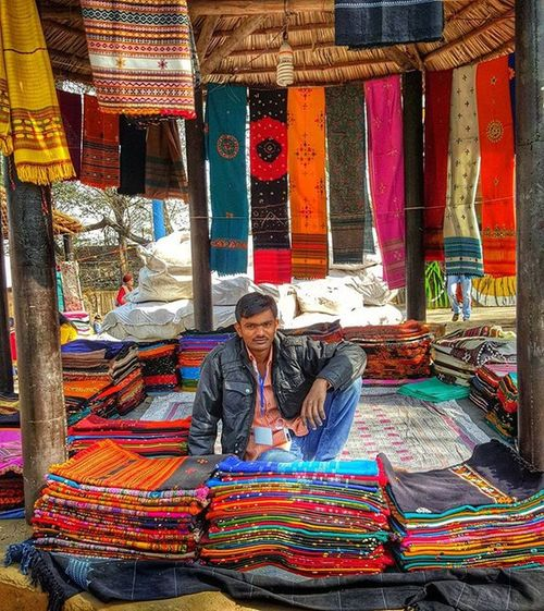 Craftsman selling his creation at Surajkund Craft Mela Craftfestival Art Colors Textile Clothes Colorful Incredibleindia Indiapictures IndiaTravelDiaries HumansOfIndia Lonelyplanetindia @streets.of.india @india.clicks @millionshadesofindia Trader Cottageindustry