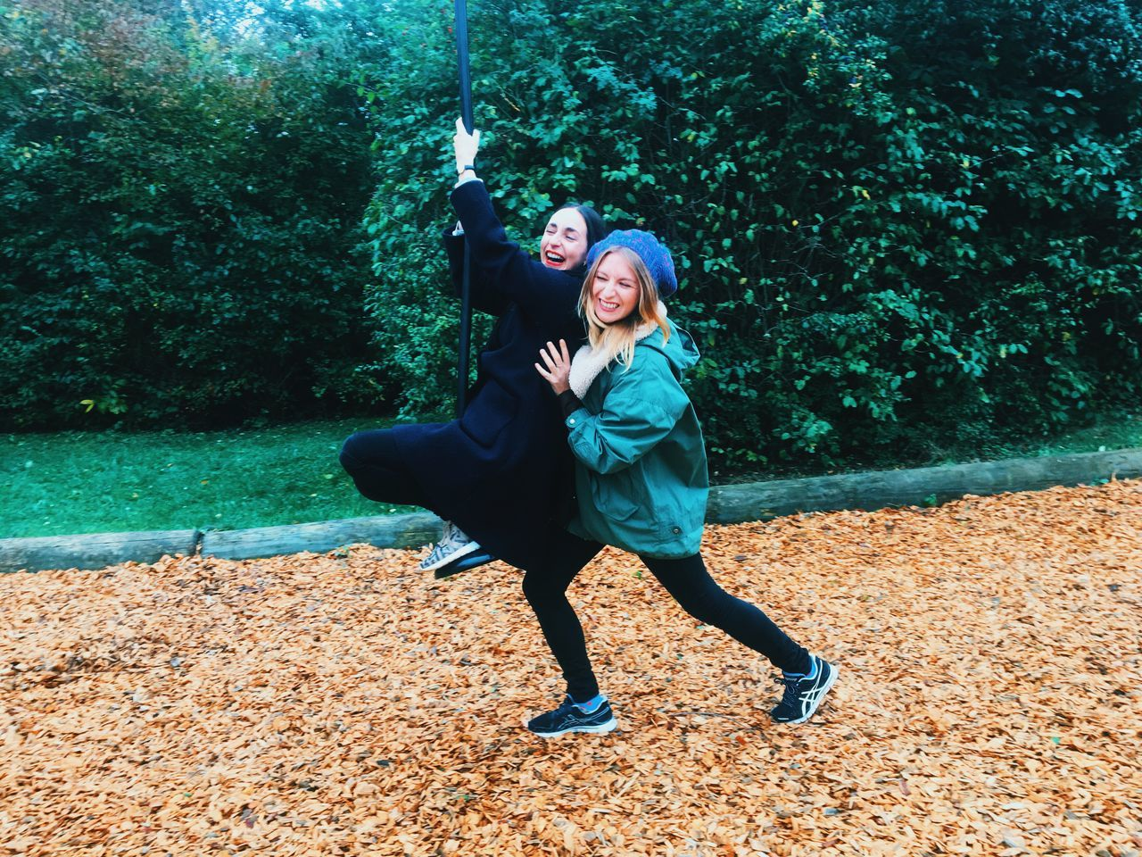 two woman on zip line Full Length Tree Person Lifestyles Young Adult Leisure Activity Young Women Casual Clothing Park - Man Made Space Nature Day Looking At Camera Vacations Outdoors Autumn Smiling Laughing Playground Zip Line Tranquility Carefree Scenics