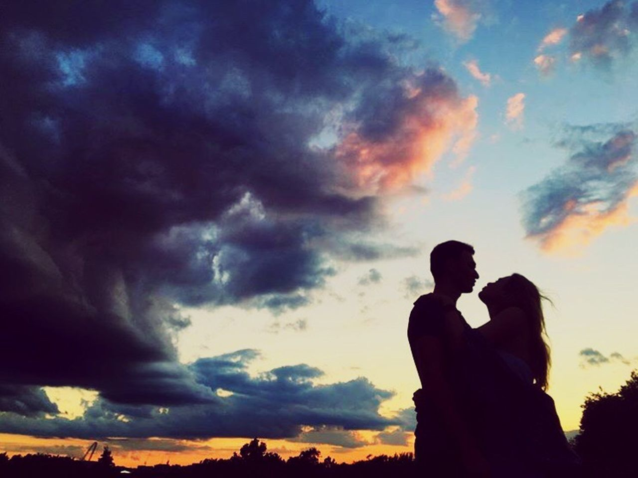 love, sunset, two people, togetherness, silhouette, cloud - sky, bonding, sky, romance, men, low angle view, nature, embracing, beauty in nature, couple - relationship, outdoors, scenics, real people, women, adult, people, young adult, adults only, day