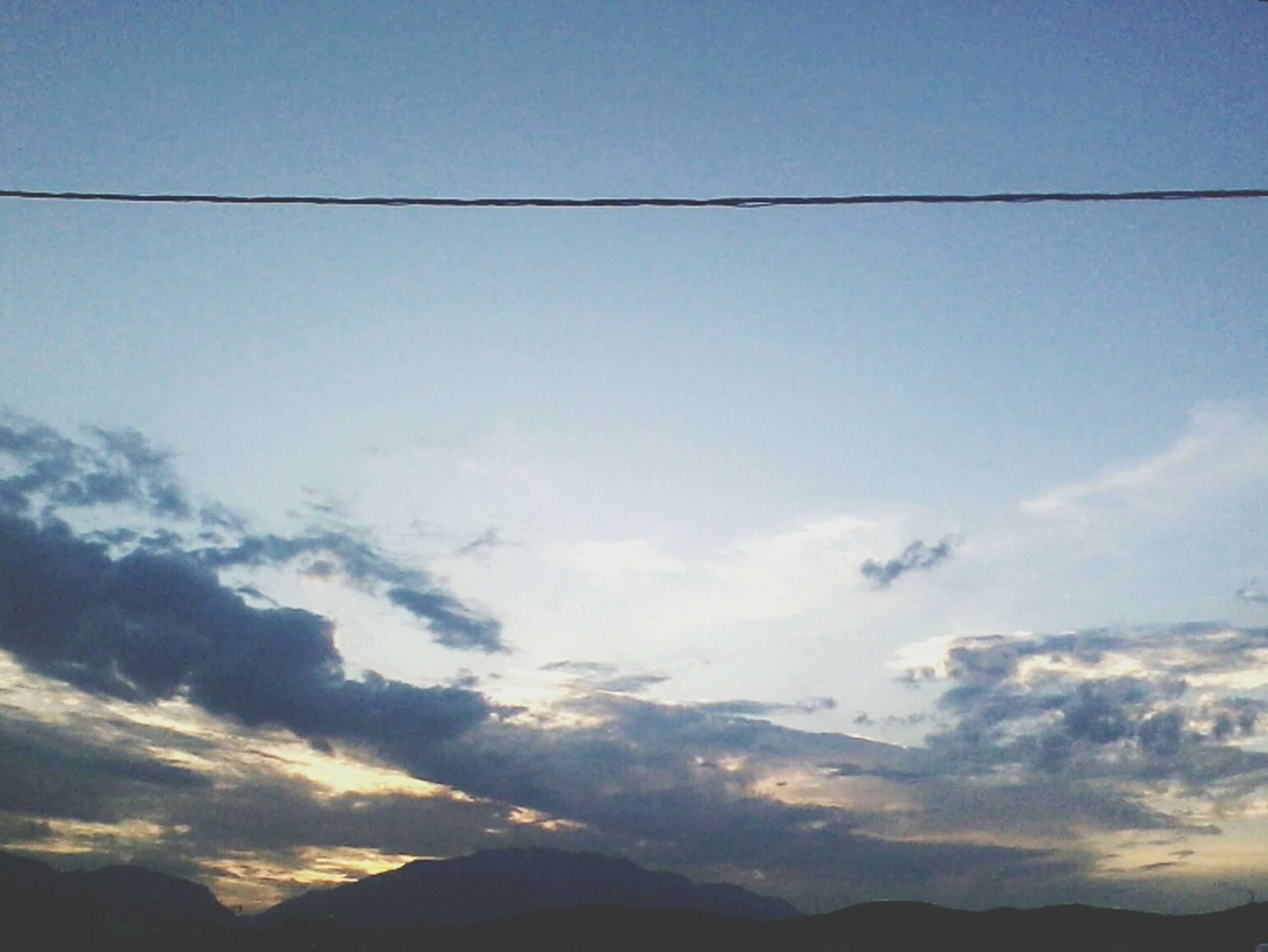 sky, tranquil scene, tranquility, scenics, beauty in nature, mountain, landscape, nature, cloud - sky, silhouette, cloud, blue, idyllic, low angle view, mountain range, sunset, outdoors, no people, copy space, non-urban scene