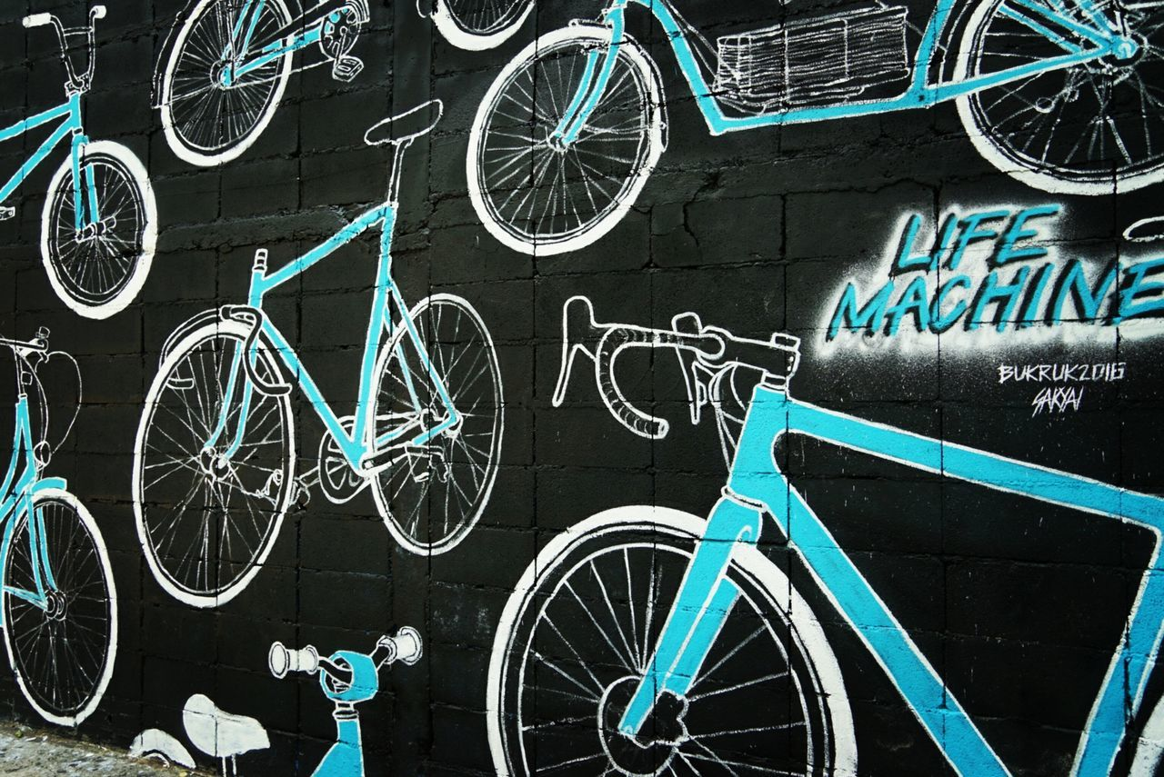 bicycle, stationary, transportation, no people, communication, outdoors, wheel, bicycle rack, day, blackboard, architecture