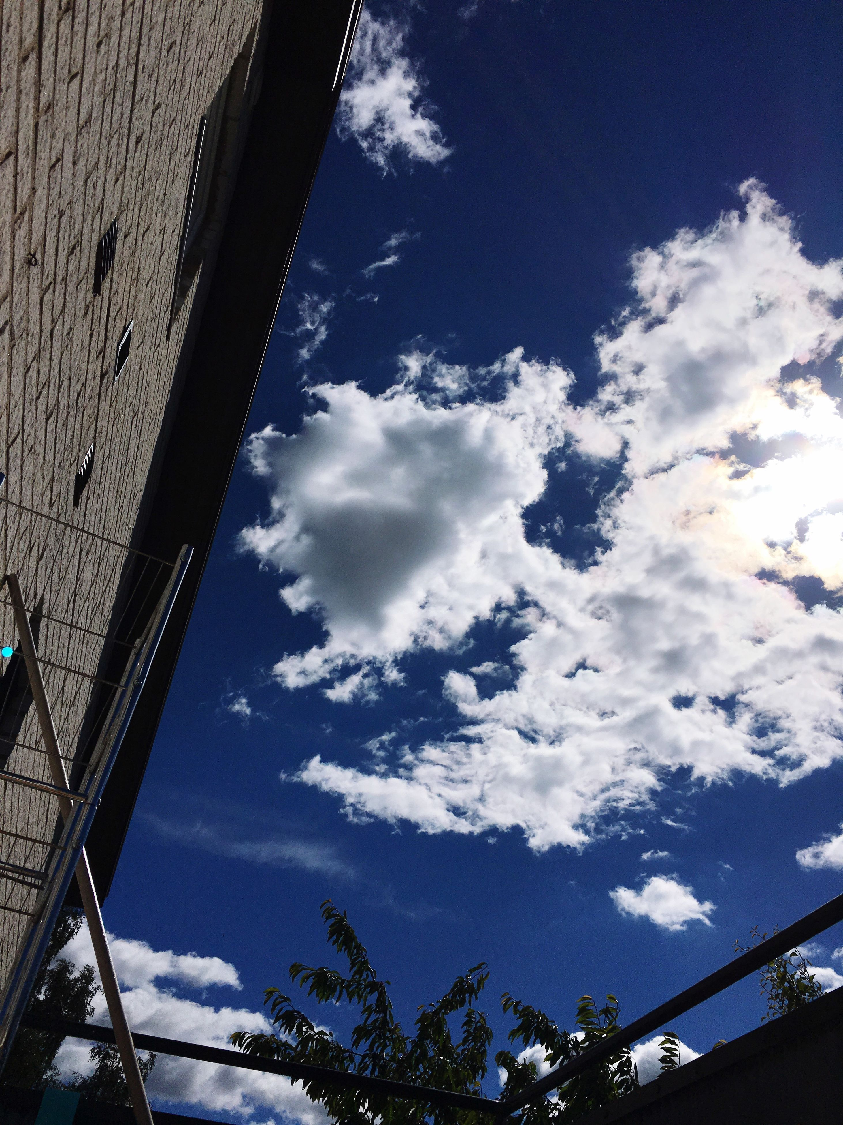 low angle view, sky, cloud - sky, built structure, architecture, cloudy, cloud, blue, high section, day, outdoors, no people, nature, weather, beauty in nature, tranquility, scenics