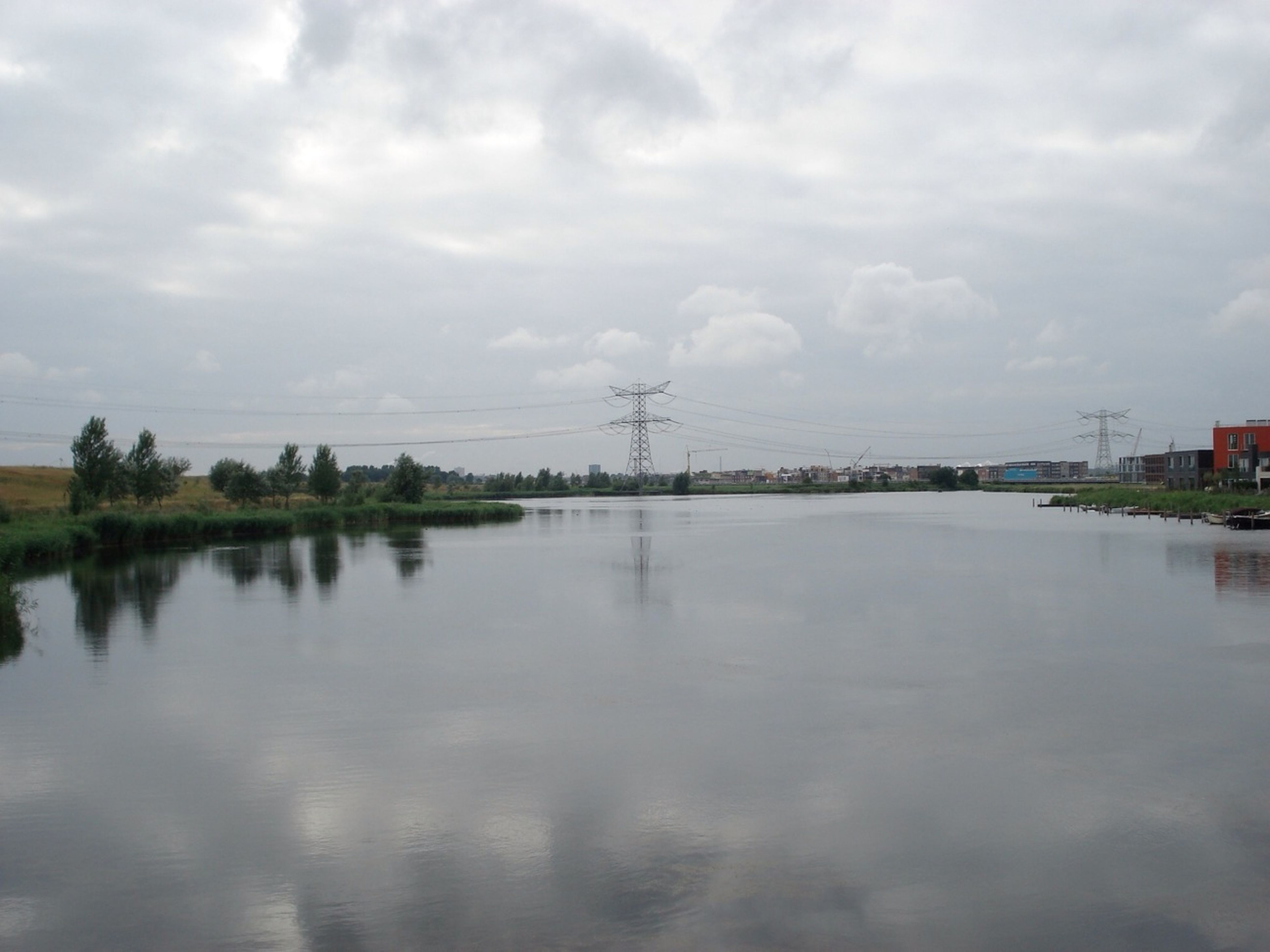 water, sky, cloud - sky, reflection, waterfront, cloudy, tranquility, tranquil scene, lake, scenics, nature, cloud, beauty in nature, weather, river, overcast, day, power line, connection, outdoors