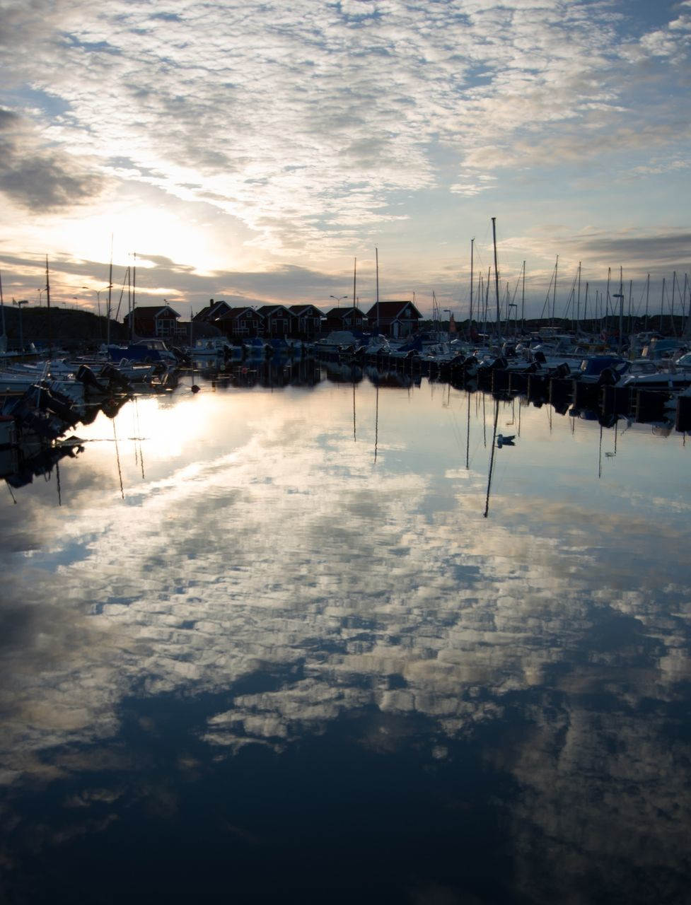 Boats Moored In Lake With Cloudy Sky Reflection