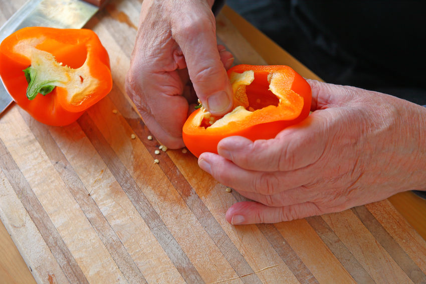 Overhead of man seeding bell pepper Copy Space Hands Man Natural Light Seeds Textures Bell Pepper Closeup Cutting Board Fingers Food Preparation Healthy Eating Holding Indoors  Kitchen Skills One Person Orange Color Room For Text Senior Adult Studio Shot Vegetable Wood Surface