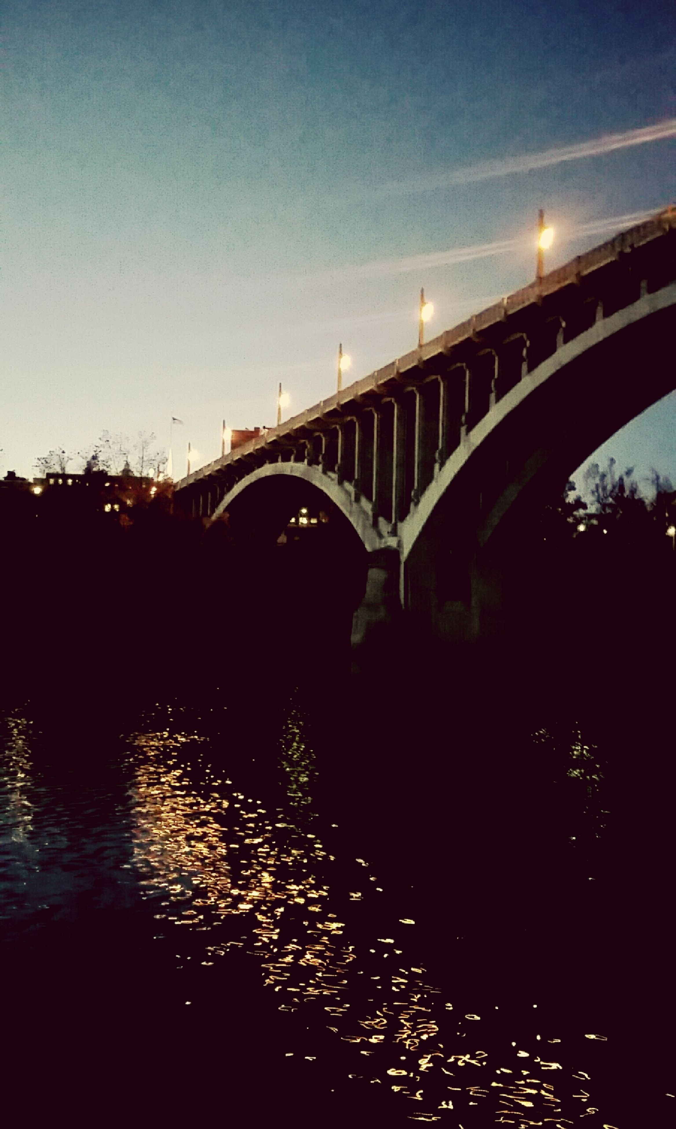 architecture, built structure, connection, bridge - man made structure, water, river, bridge, engineering, illuminated, sky, building exterior, night, clear sky, reflection, waterfront, transportation, arch bridge, city, outdoors, no people