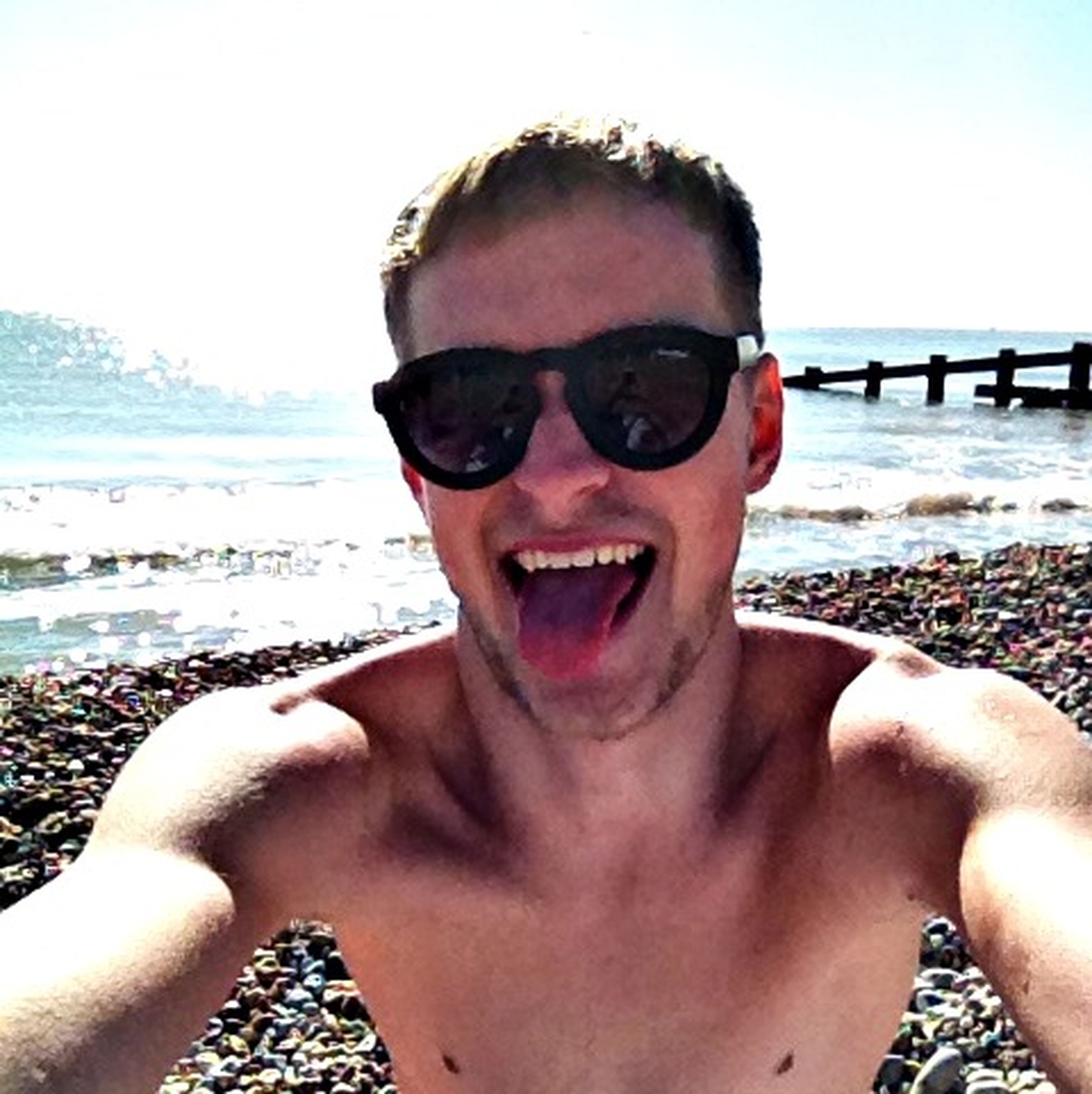 sunglasses, portrait, beach, lifestyles, looking at camera, person, leisure activity, young adult, headshot, sea, water, front view, young men, shore, sky, close-up, head and shoulders, sunlight